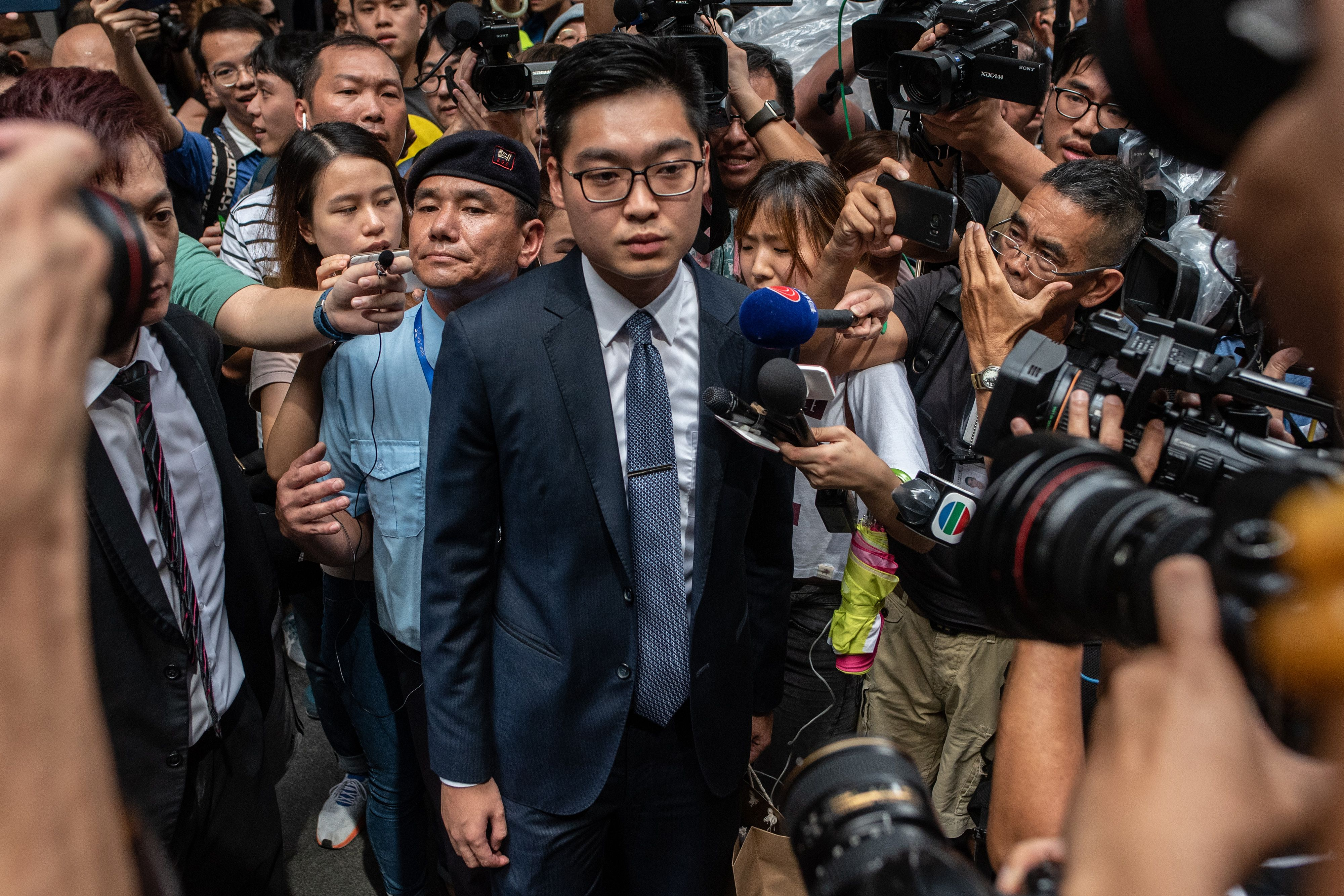 Andy Chan (C), founder of the Hong Kong National Party, is surrounded by members of the media as he leaves the Foreign Correspondents' Club in Hong Kong on Aug. 14, 2018.