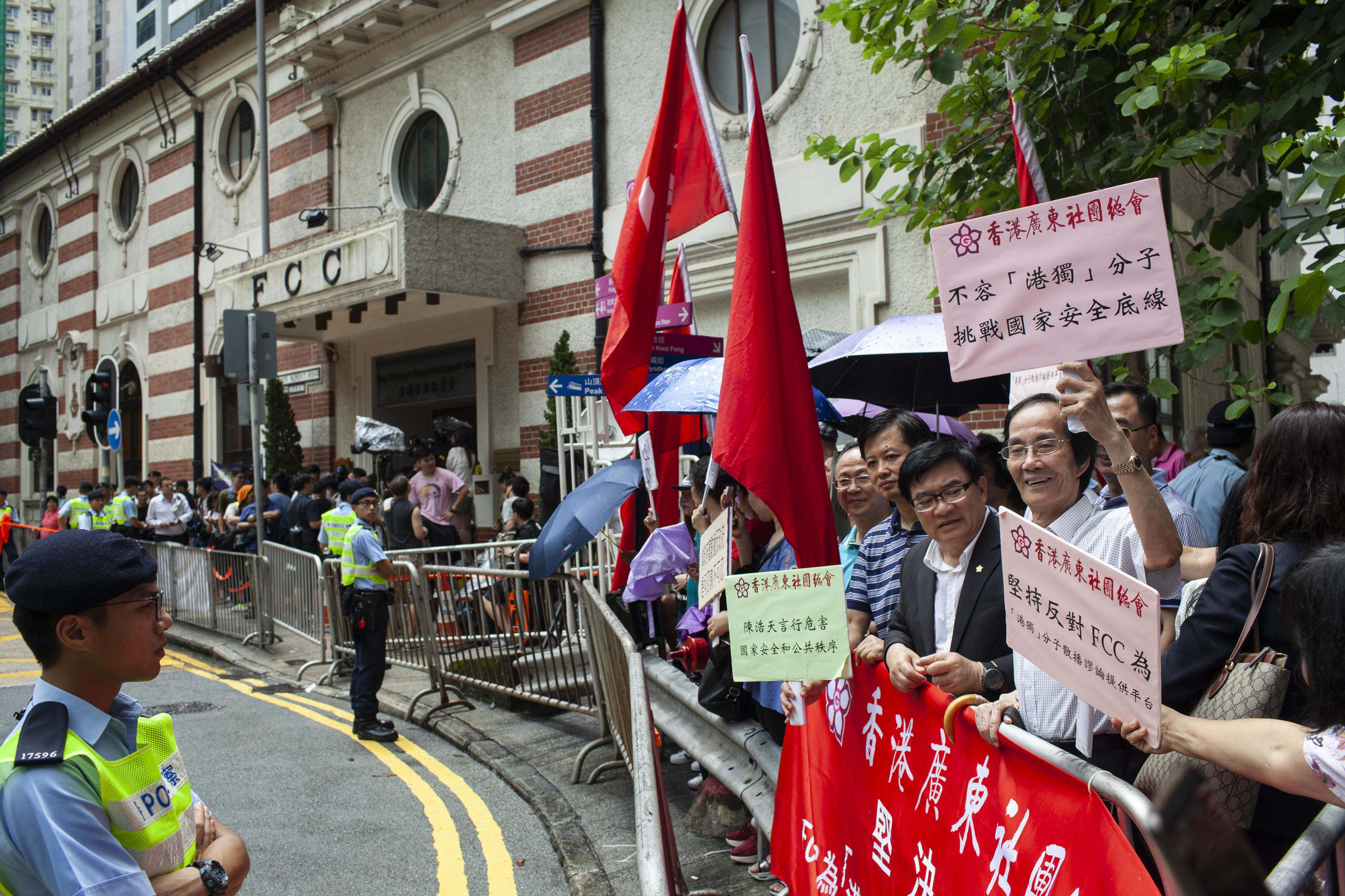 Pro-China demonstrators hold signs outside the Foreign Correspondents Club in Hong Kong on Aug. 13, 2018.