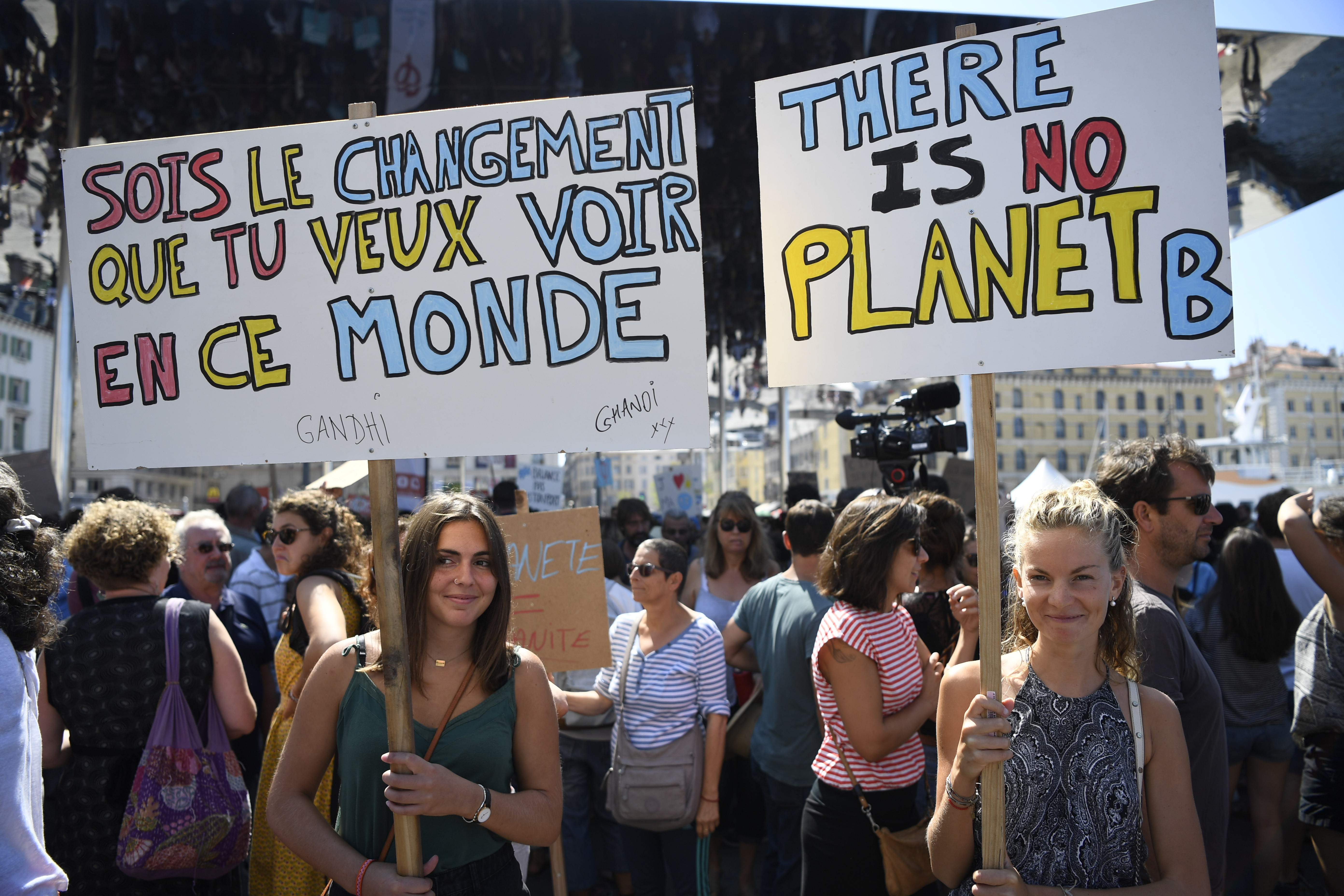 People hold banners as they take part in a march on September 8, 2018 in Marseille, southern France, as part of a global day of action  Rise For Climate.