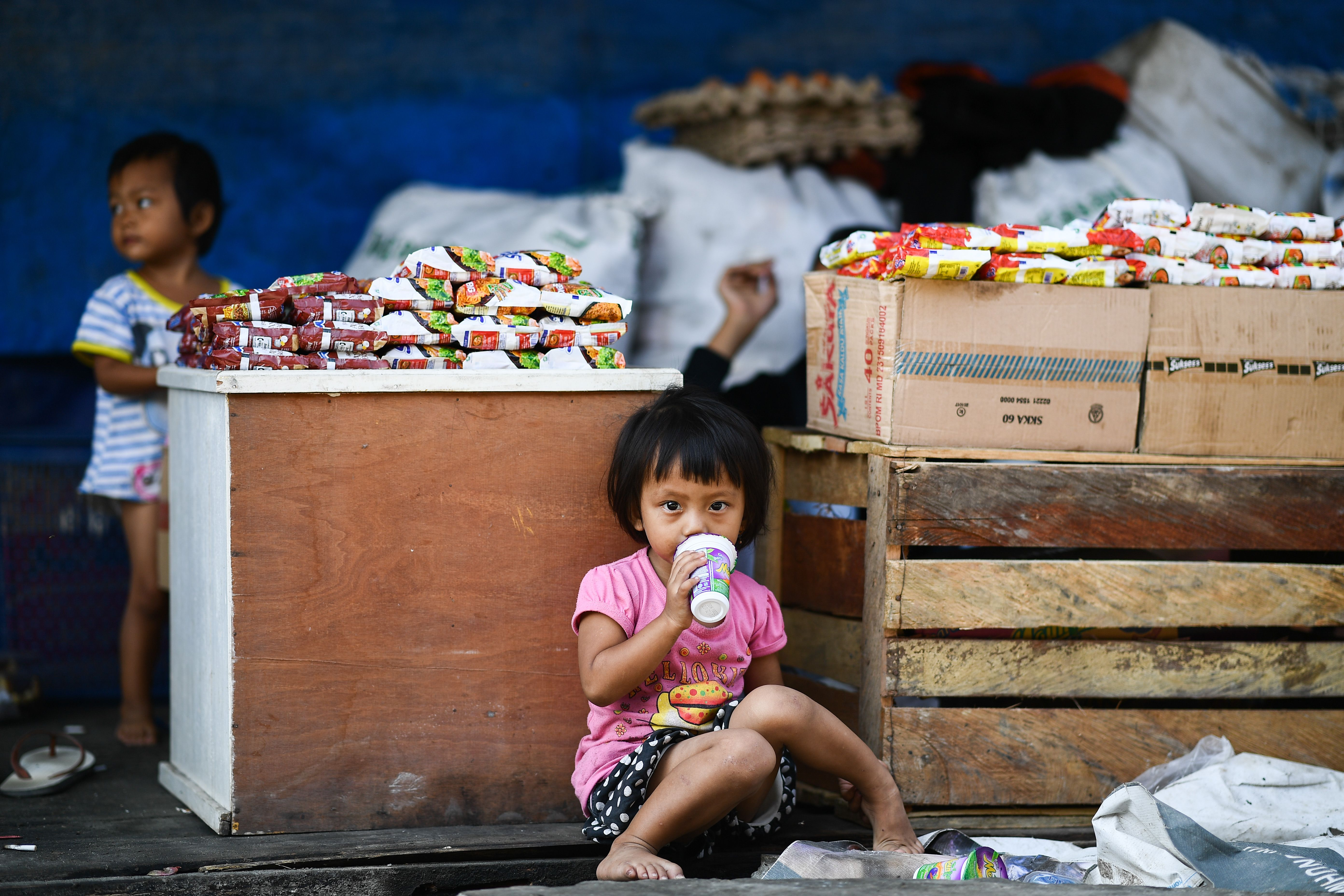 A child drinks juice at their family shop in a traditional bazar in Palu in Indonesia's Central Sulawesi on Oct. 4, 2018.