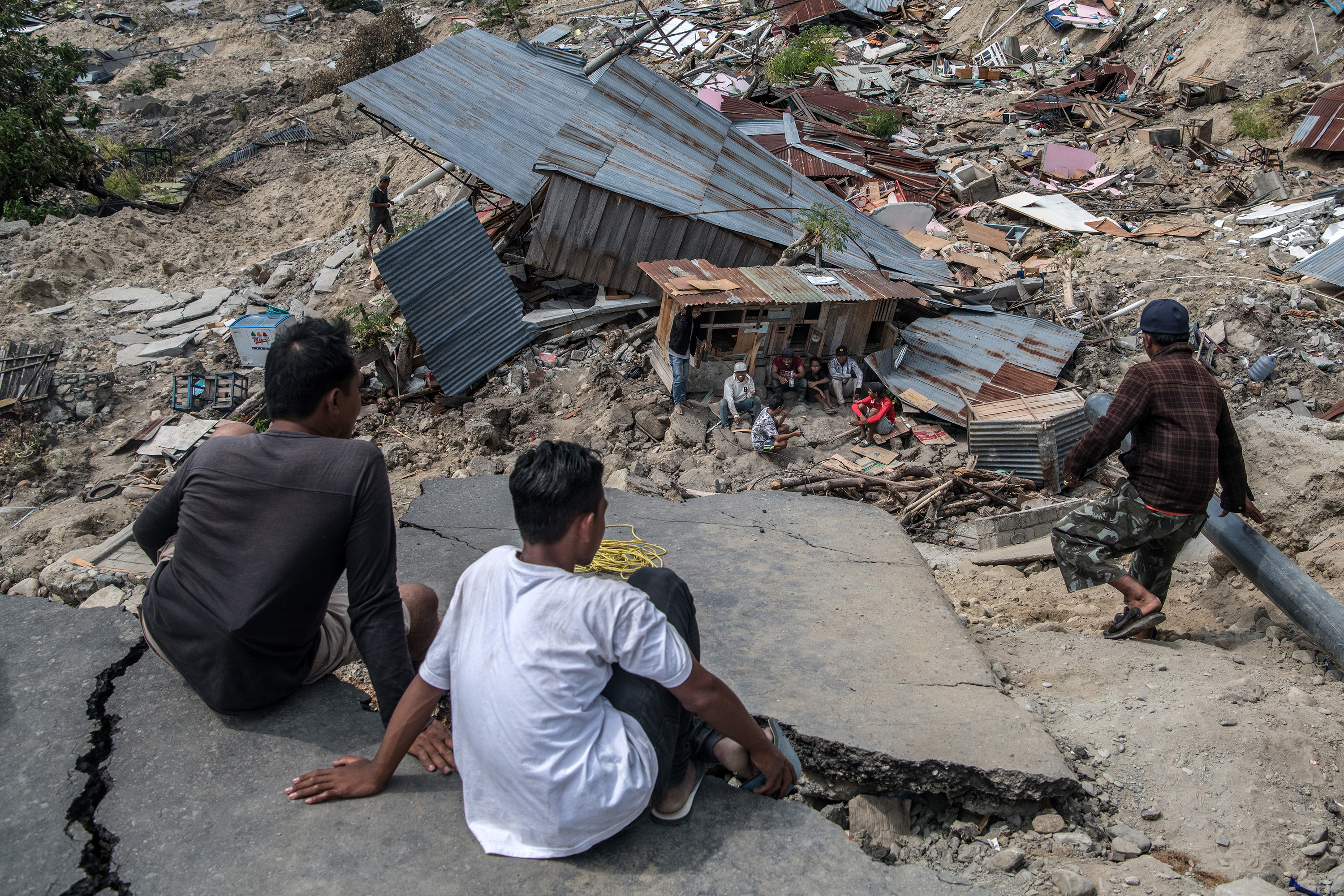People look down from the edge of ruined road to a group of men resting in the shade of shack in the remains of an area that was completely destroyed by an earthquake, on Oct. 4, 2018 in Palu, Indonesia