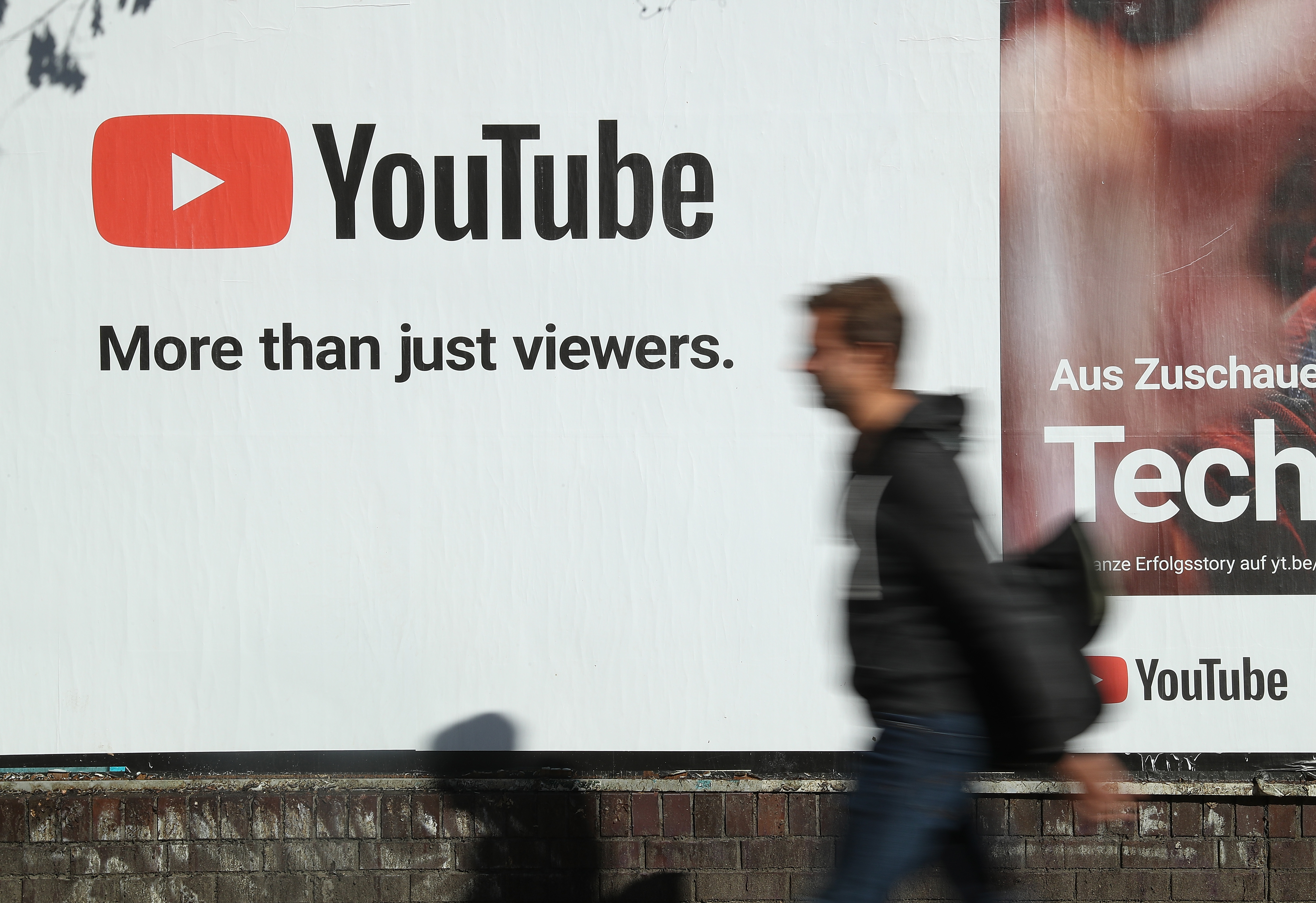 A man walks past a billboard advertisement for YouTube in Berlin, Germany. on on Oct. 5, 2018.