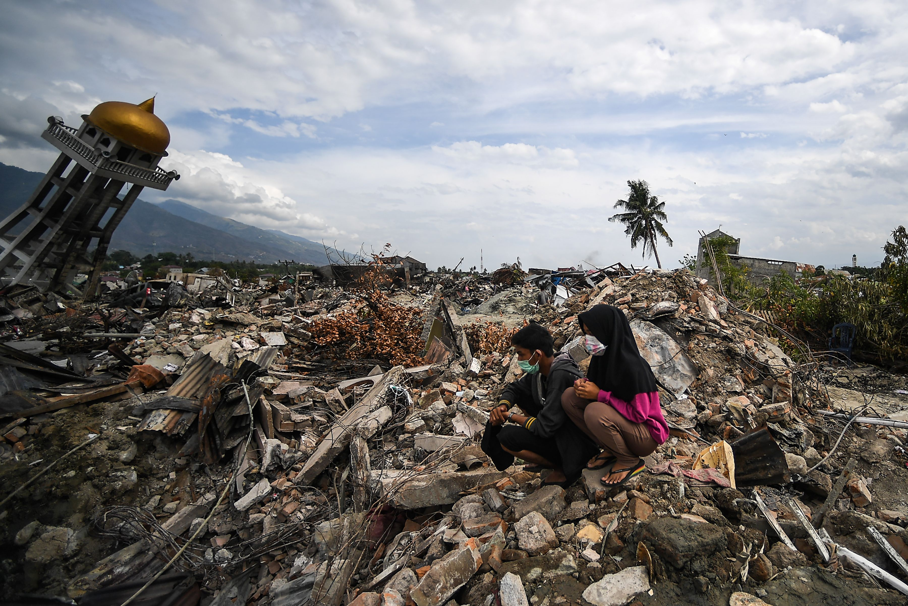 Residents sit among debris at Perumnas Balaroa village in Palu in Indonesia's Central Sulawesi on Oct. 6, 2018.