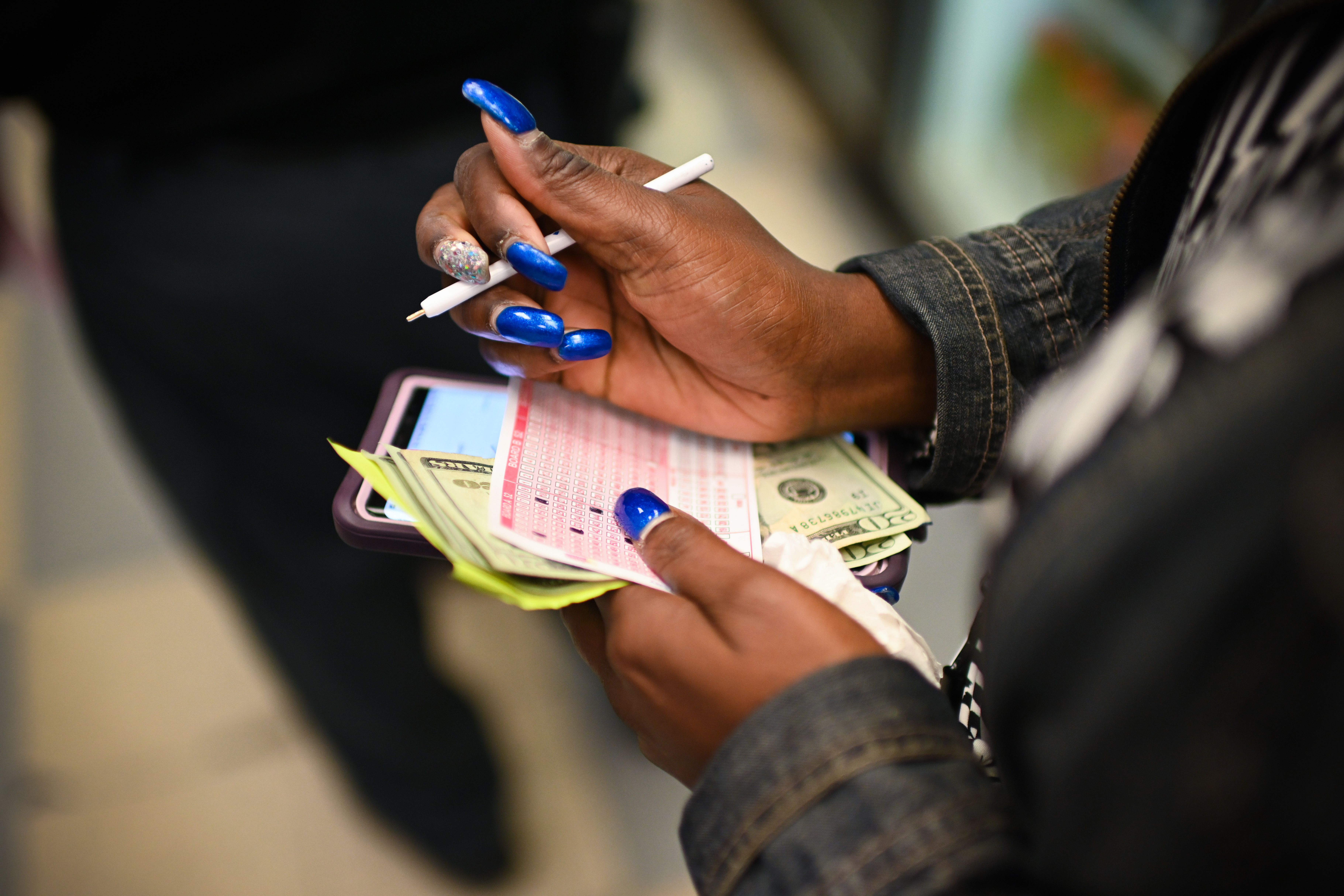 A woman buys a lottery ticket at a liquor store in Washington DC, on Oct. 23, 2018.