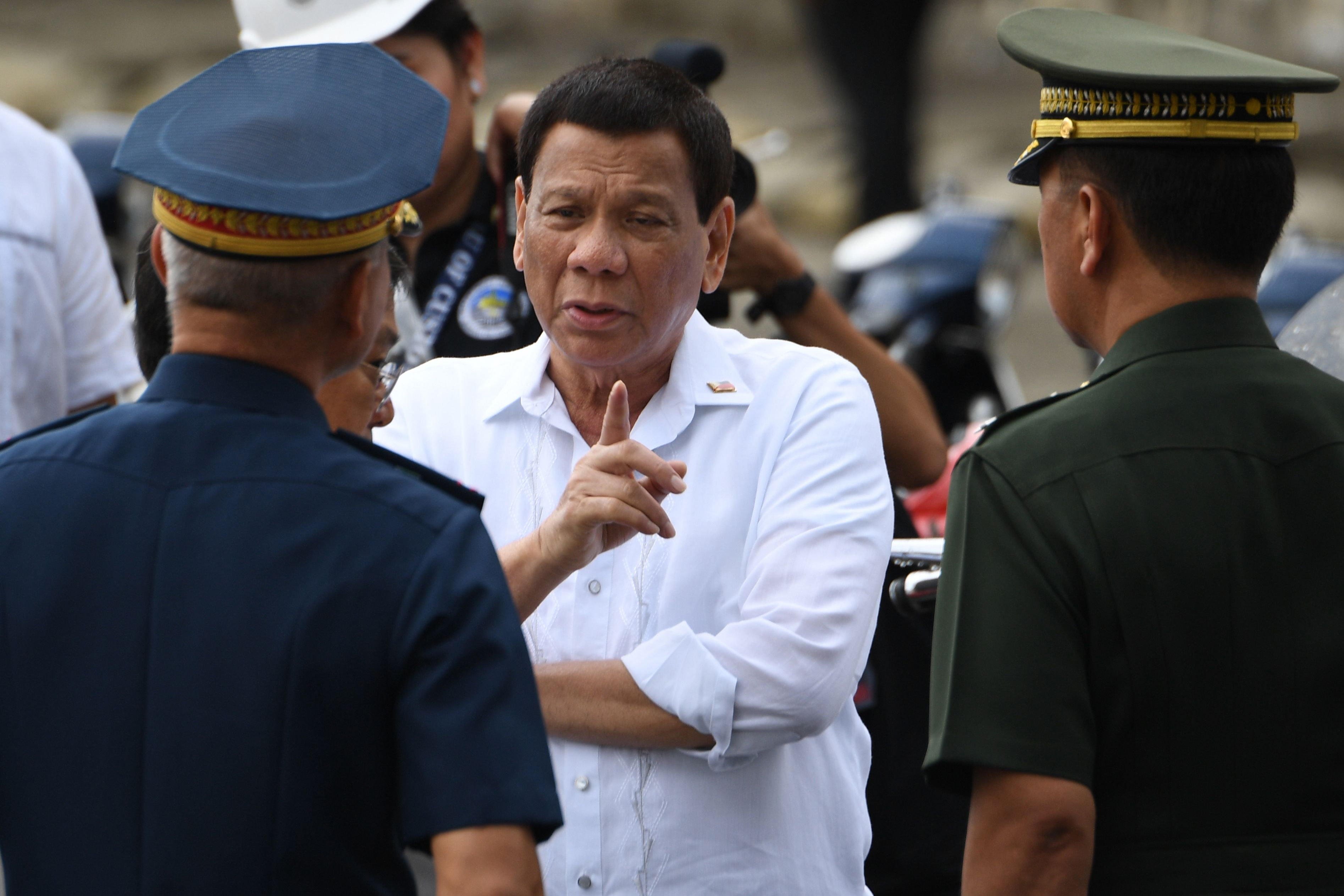 Philippine President Rodrigo Duterte (C) talks to military chief General Carlito Galvez (R) and national police chief Oscar Albayalde (L) in Manila on May 30, 2018.