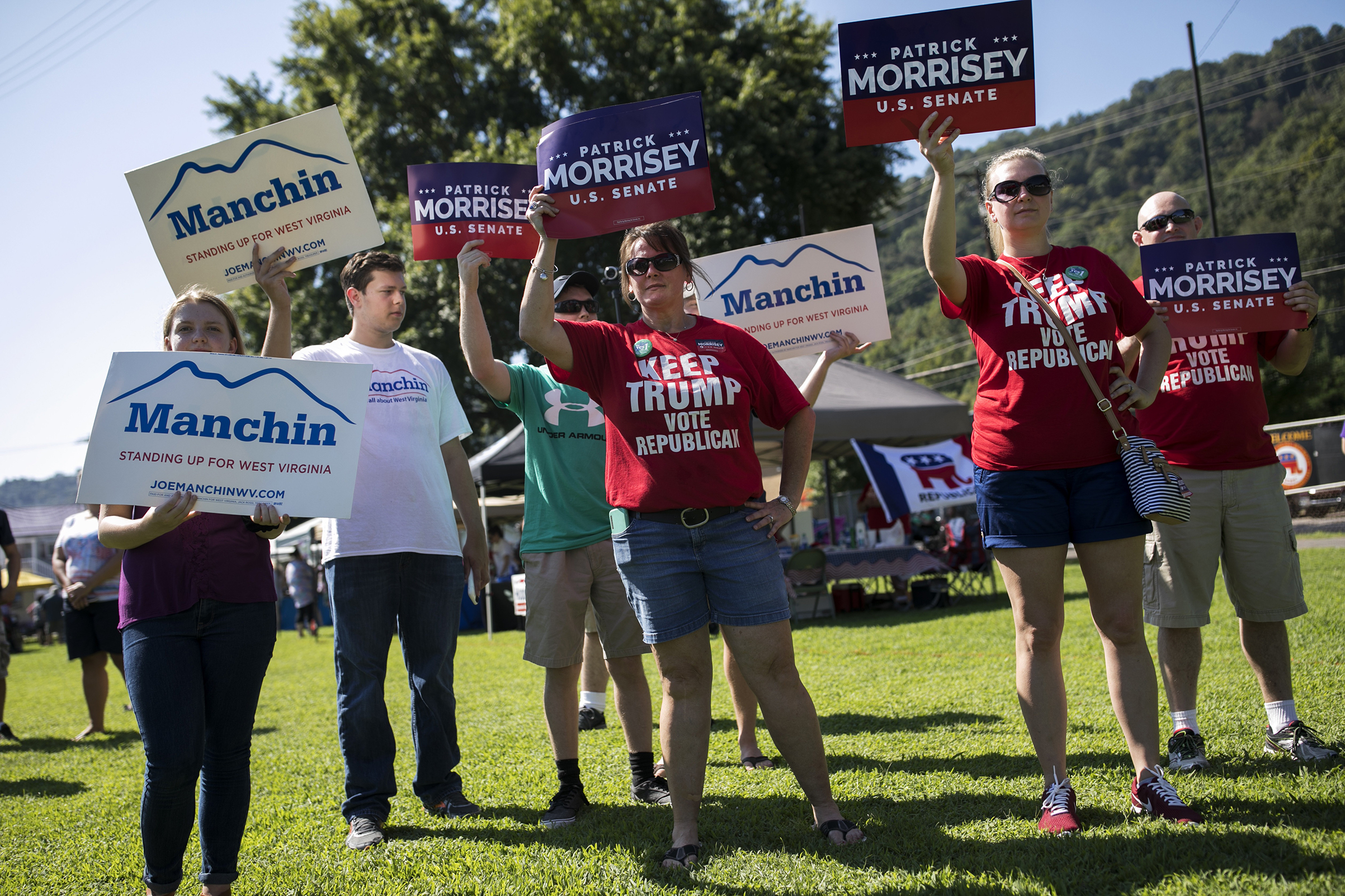 Demonstrators campaign on Sept. 3 in Marmet, W.Va., in a Senate race that has centered on health care