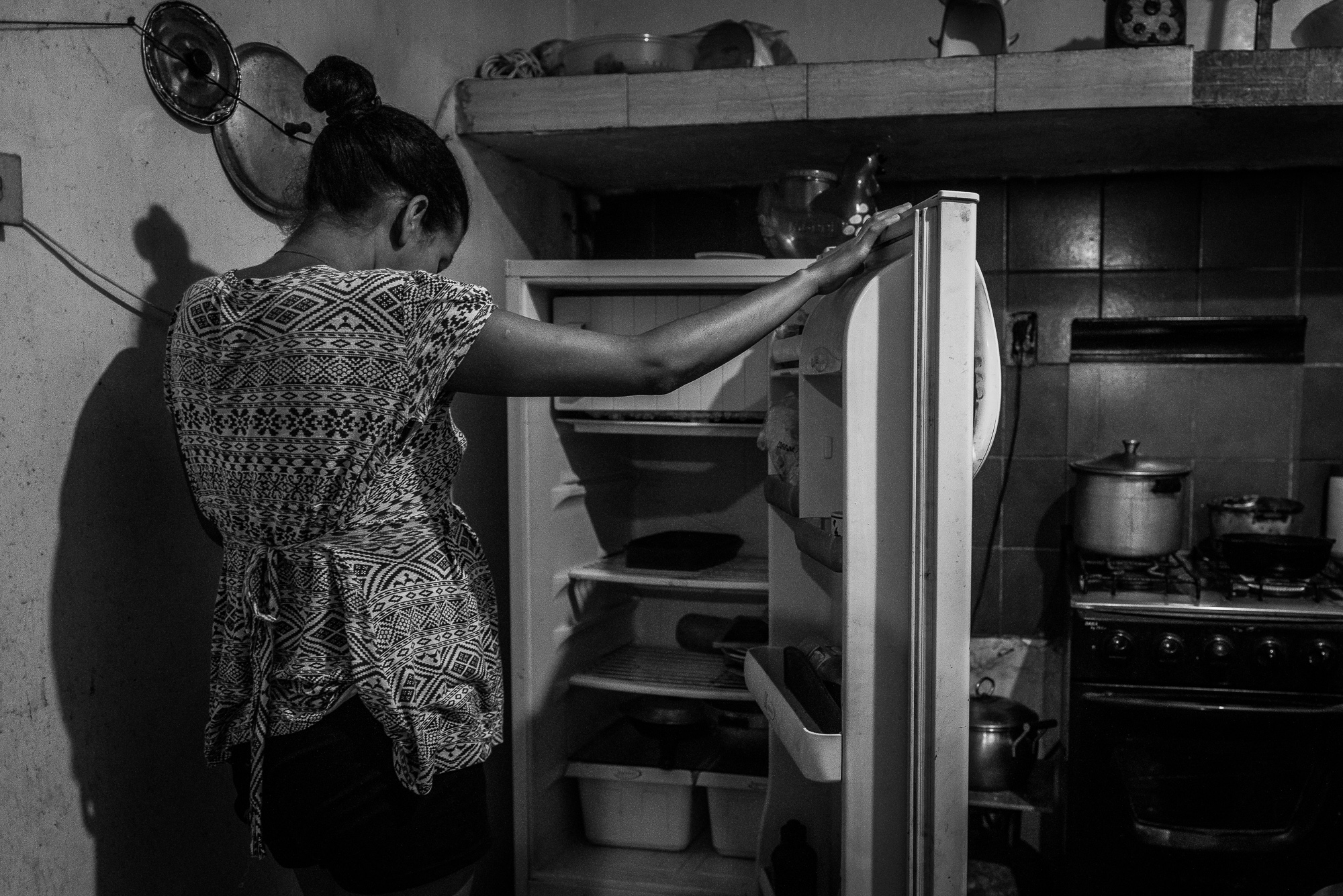 A woman stares at her empty fridge in Petare. For many families, even the most basic items, such as tomatoes and beans, are hard to come by.