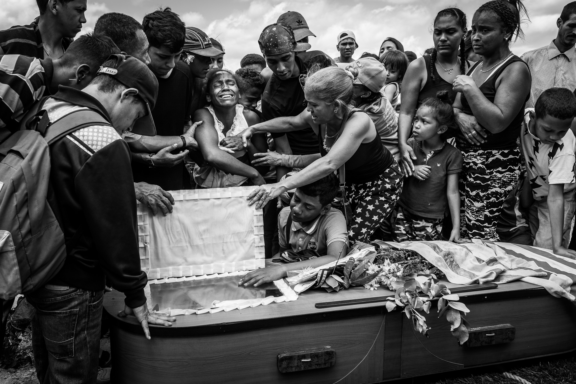 A woman cries during the funeral of her husband Keiber Cubero, 25, who was allegedly executed by police after he was caught robbing a restaurant, in search of food.