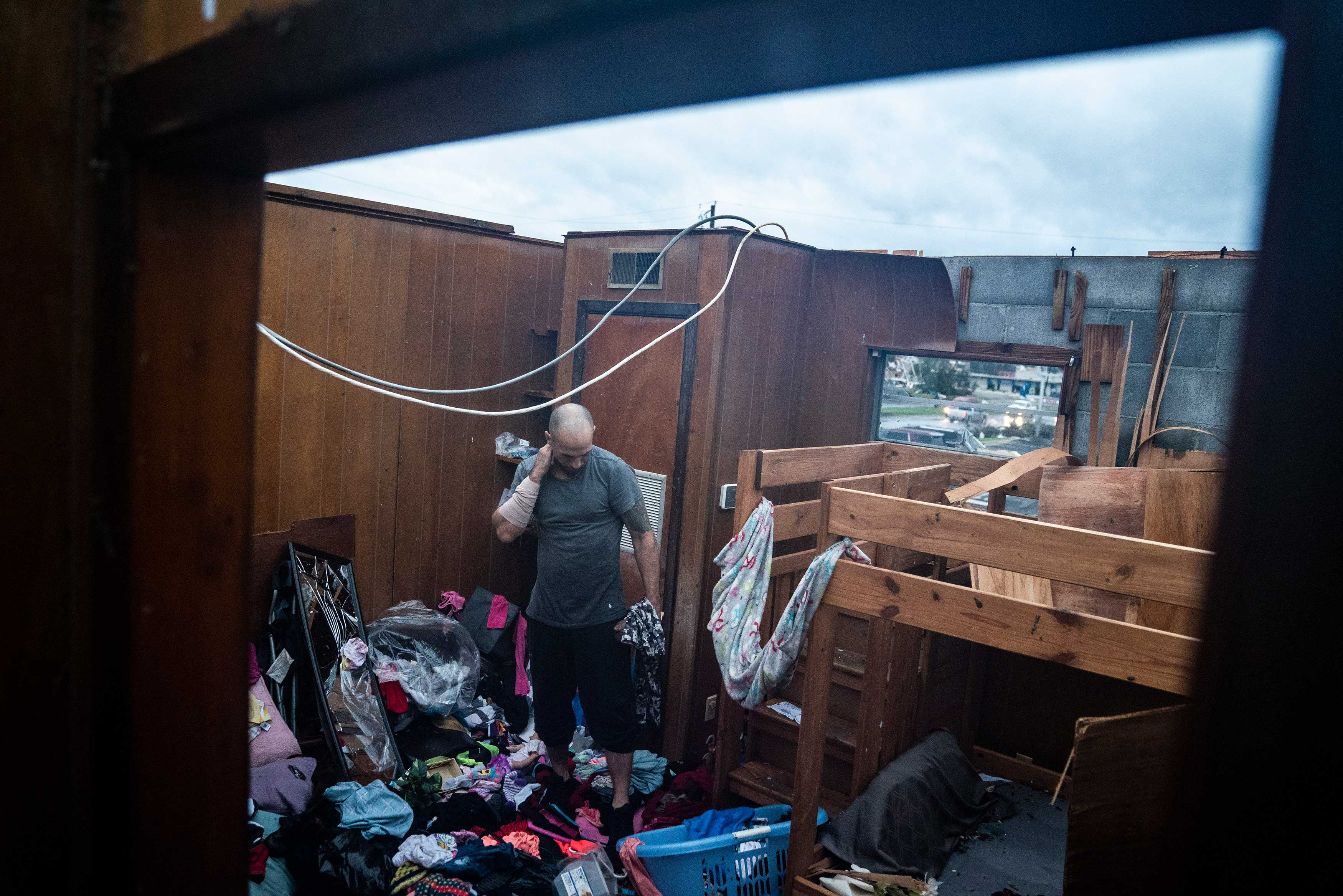 Jason Phipps looks through his families roofless apartment after category 4 Hurricane Michael made land fall along the Florida panhandle, on Oct. 10, 2018 in Panama City, Fla.