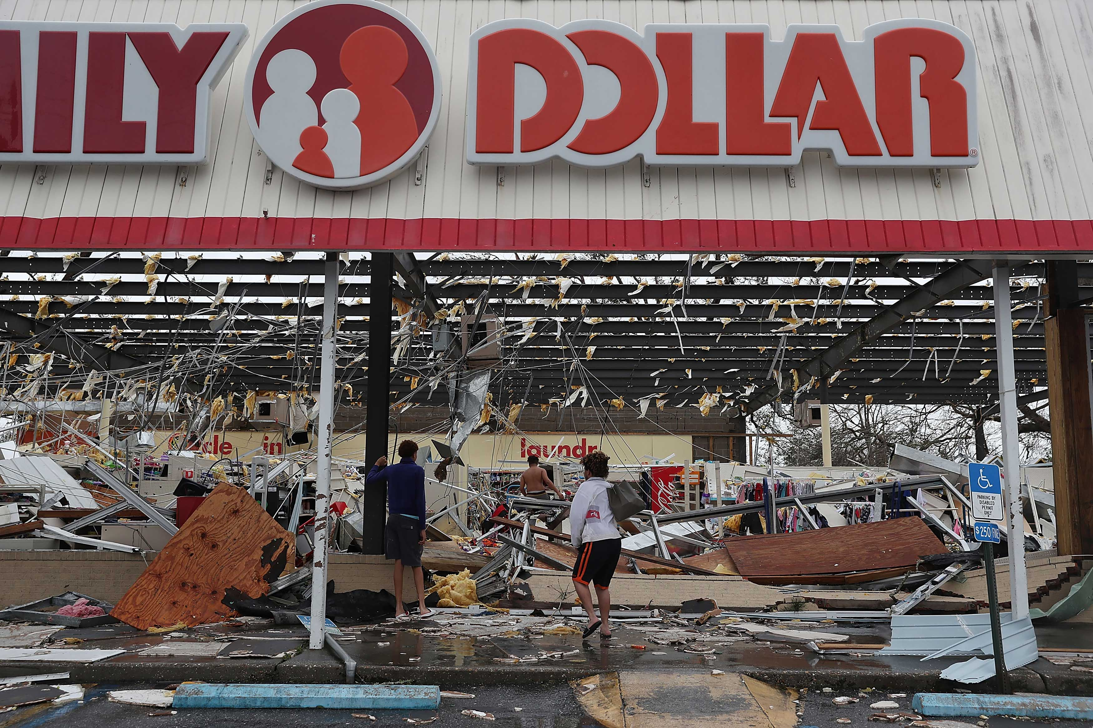 People look on at a damaged store after Hurricane Michael passed through on Oct. 10, 2018 in Panama City, Fla.