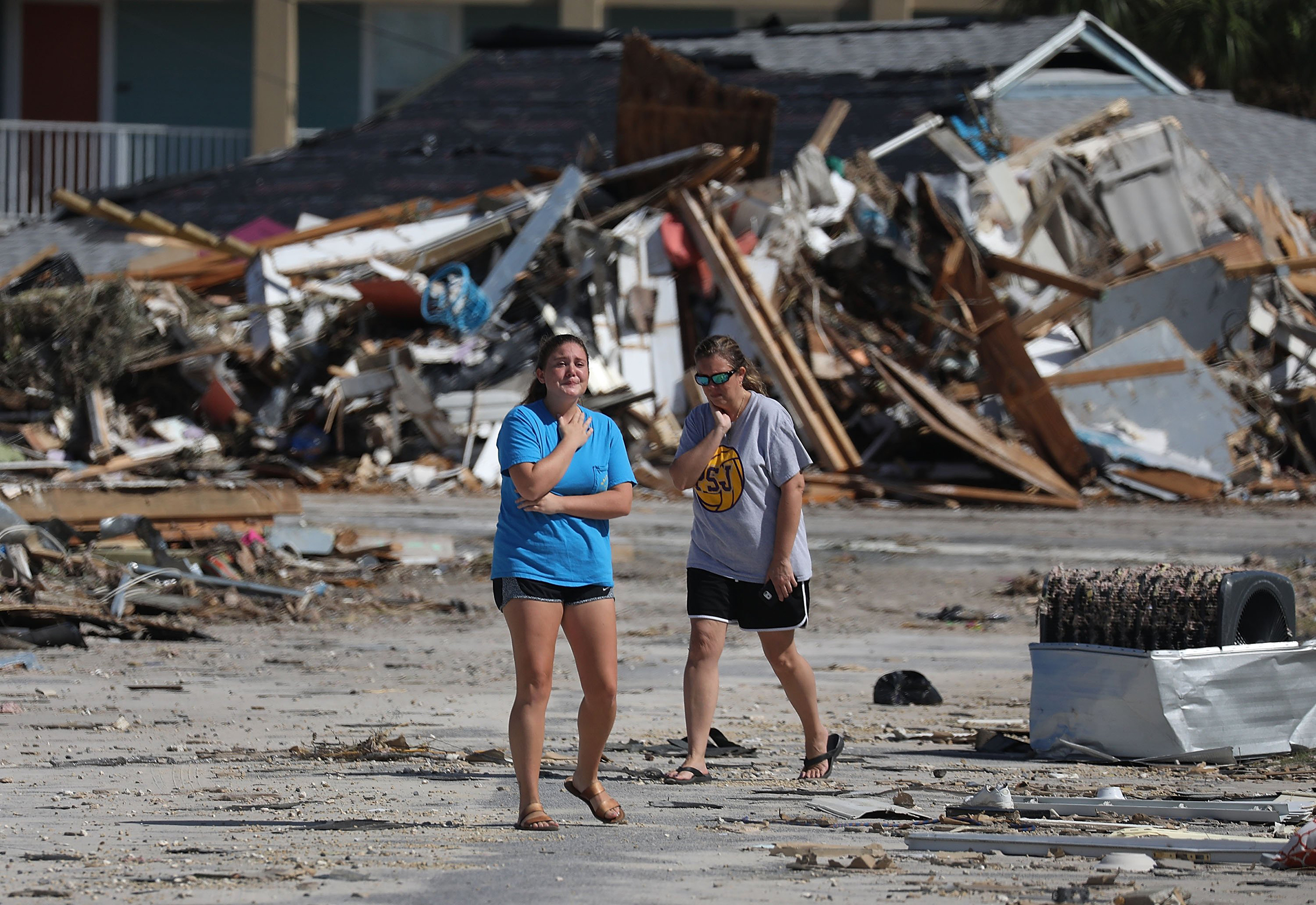 Elizabeth Hanson, right, and her daughter, look at their home that was heavily damaged when Hurricane Michael passed through the area on Oct. 11, 2018 in Mexico Beach, Fla.