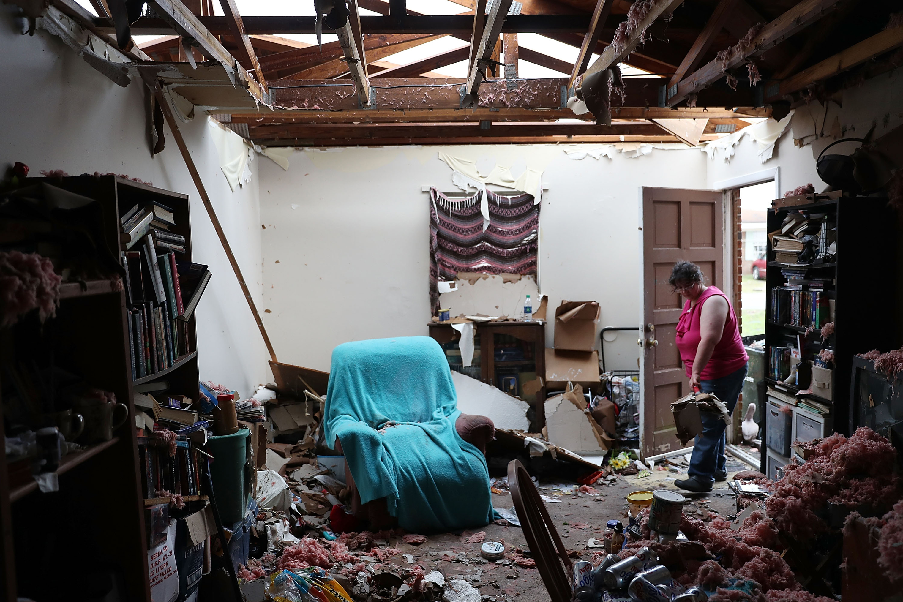 Amanda Logsdon begins the process of trying to clean up her home after the roof was blown off by the passing winds of Hurricane Michael on Oct. 11, 2018 in Panama City, Fla.