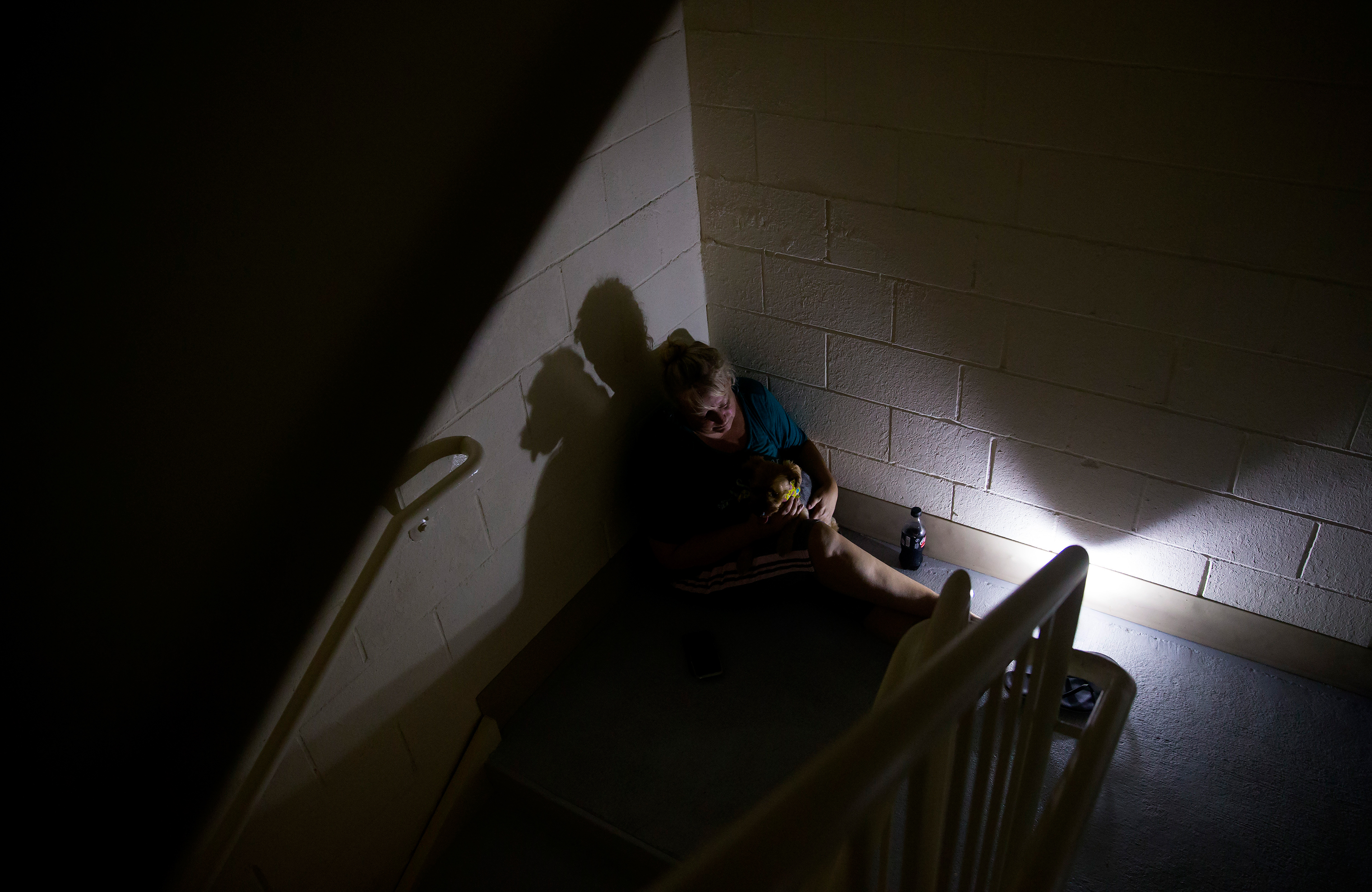 A woman rides out Hurricane Matthew in a hotel stairwell in Panama City Beach, Fla., Oct. 10, 2018.