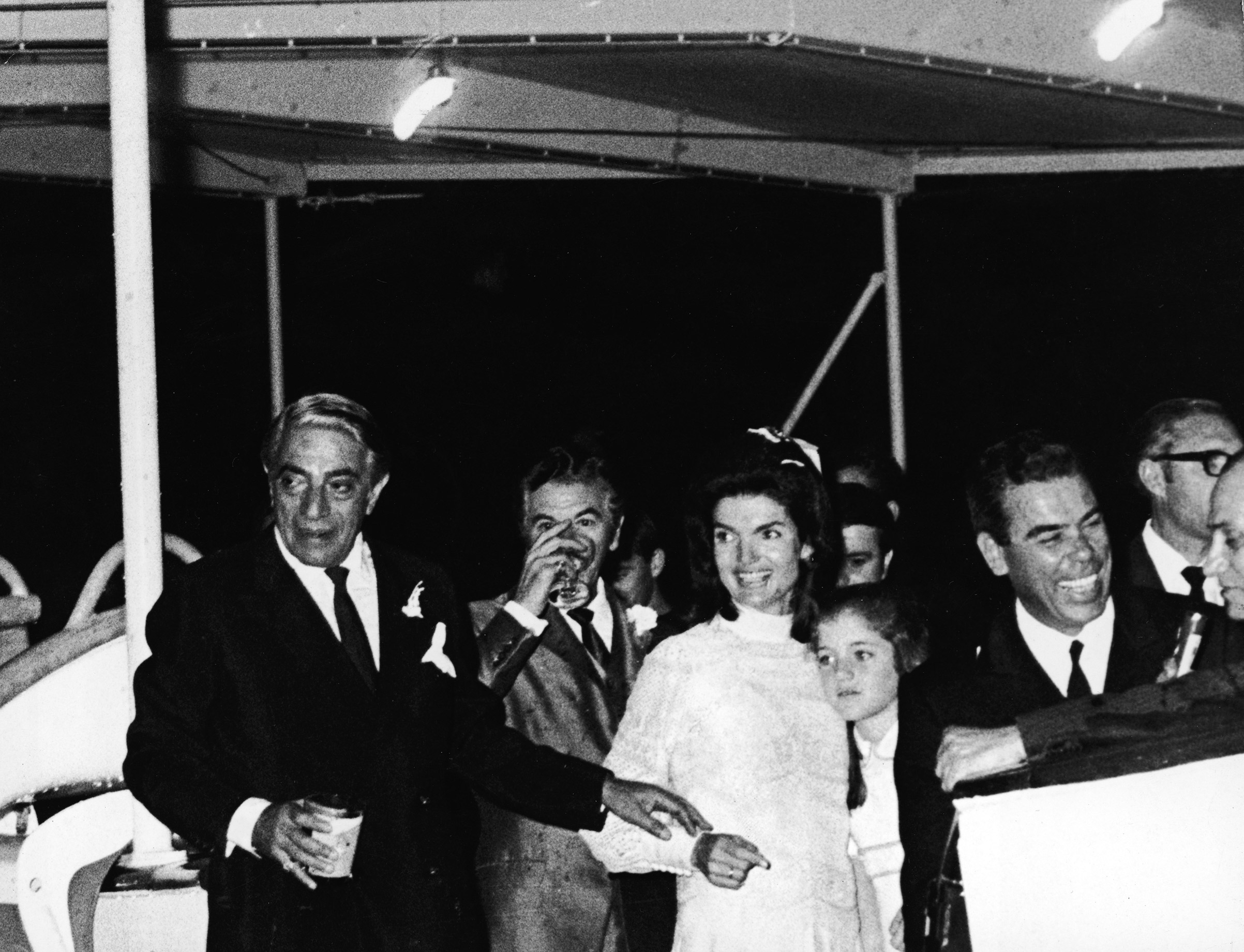 Jacqueline Kennedy Onassis, embracing her daughter, Caroline Kennedy, and her new husband, Greek shipping magnate Aristotle Onassis at their wedding reception aboard the yacht, Christina, shortly after they tied the knot on the Island of Skorpios, Greece, on Oct. 21, 1968.