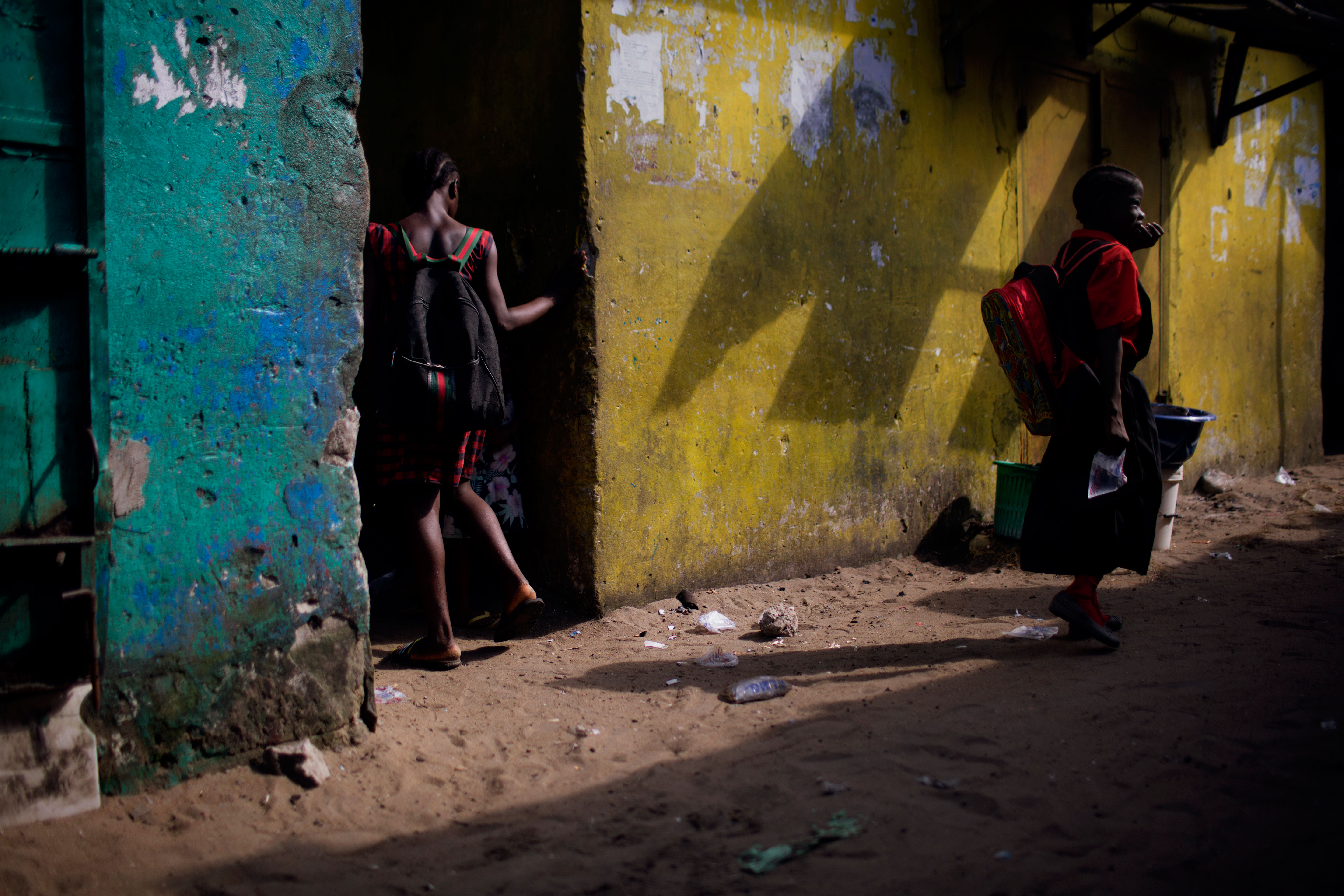 A girl wearing the More Than Me uniform walks into an alley in the West Point neighborhood of Monrovia, Liberia.
