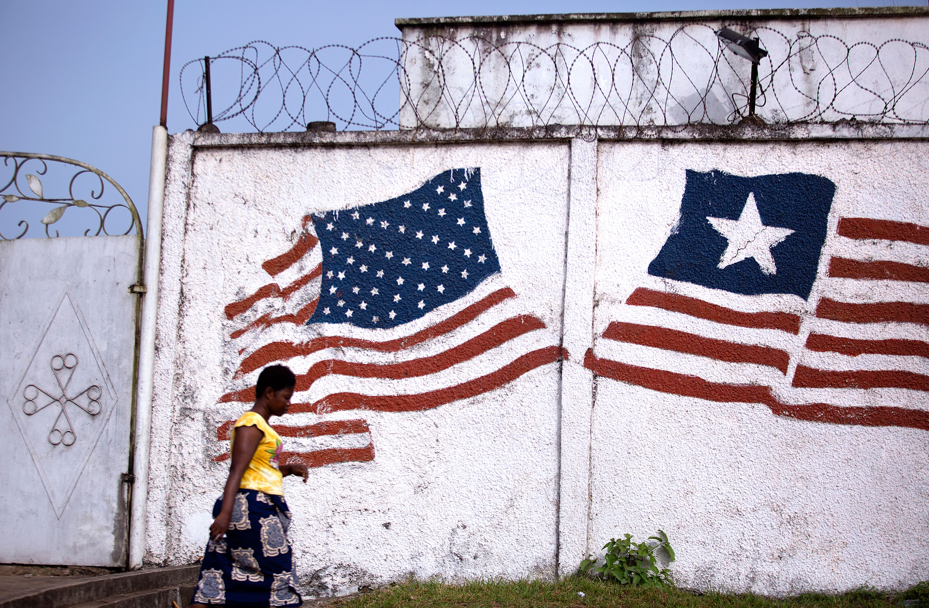 A woman in Monrovia walks past a mural of the Liberian and American flags. Liberia was formed by the American Colonization Society, an organization that resettled free African Americans and freed slaves.