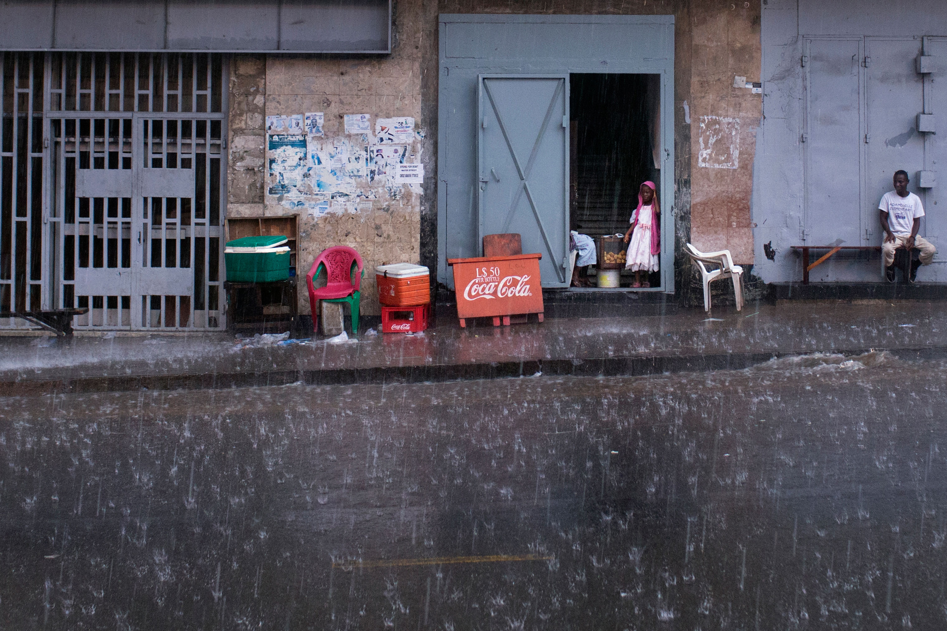 A little girl looks out onto Ashmun Street in Monrovia. Rainy season lasts more than half the year in Liberia.
