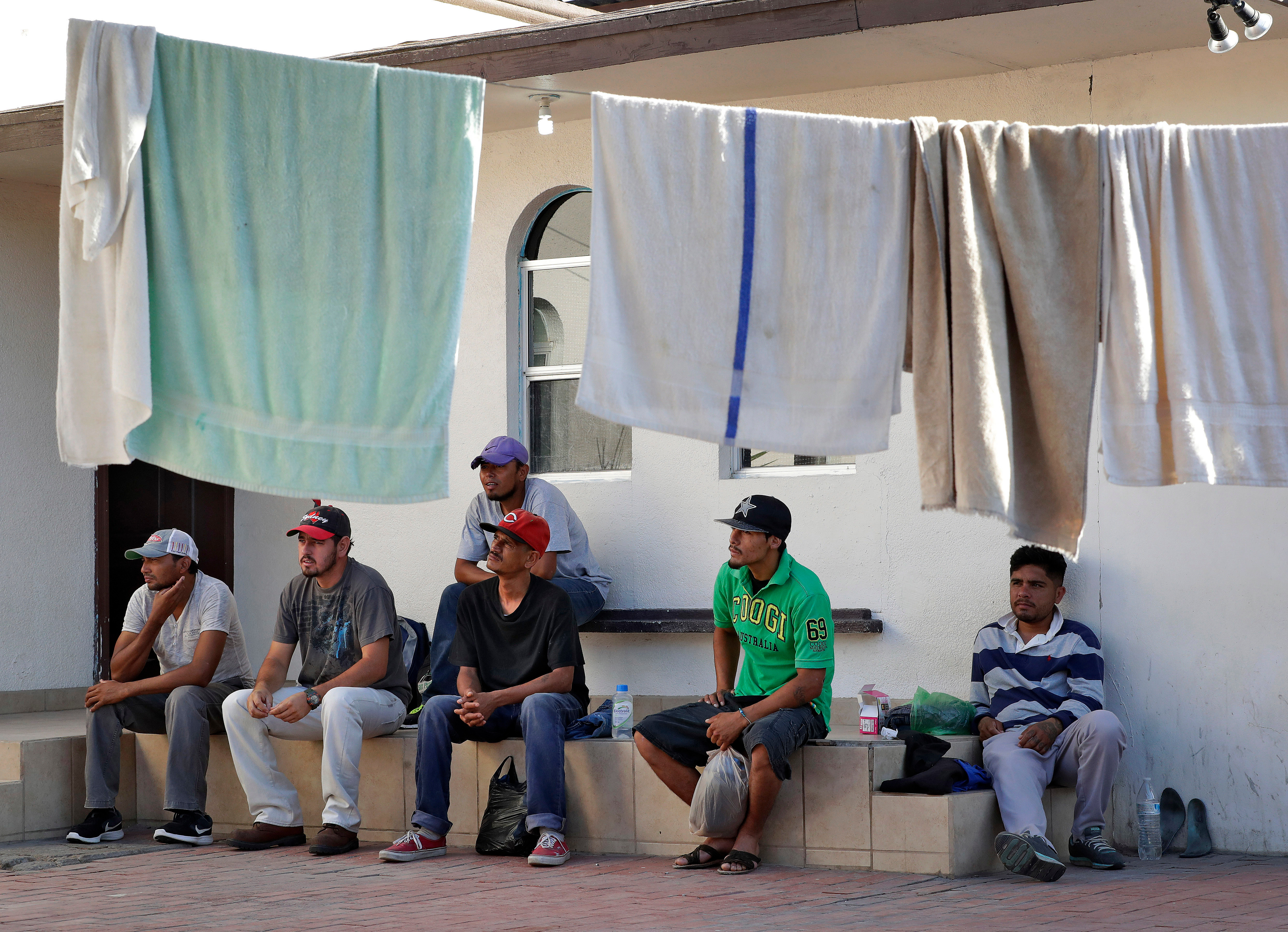 In this July 19, 2018 file photo, Central American men sit in the courtyard of the Asociacion Casa Del Migrante  La Divina Providencia  group house as their laundry dries in San Luis, Sonora, Mexico. Thousands of families and unaccompanied children are continuing to cross the U.S. border in Arizona and California even after learning of the government's family separation policy upon apprehension.