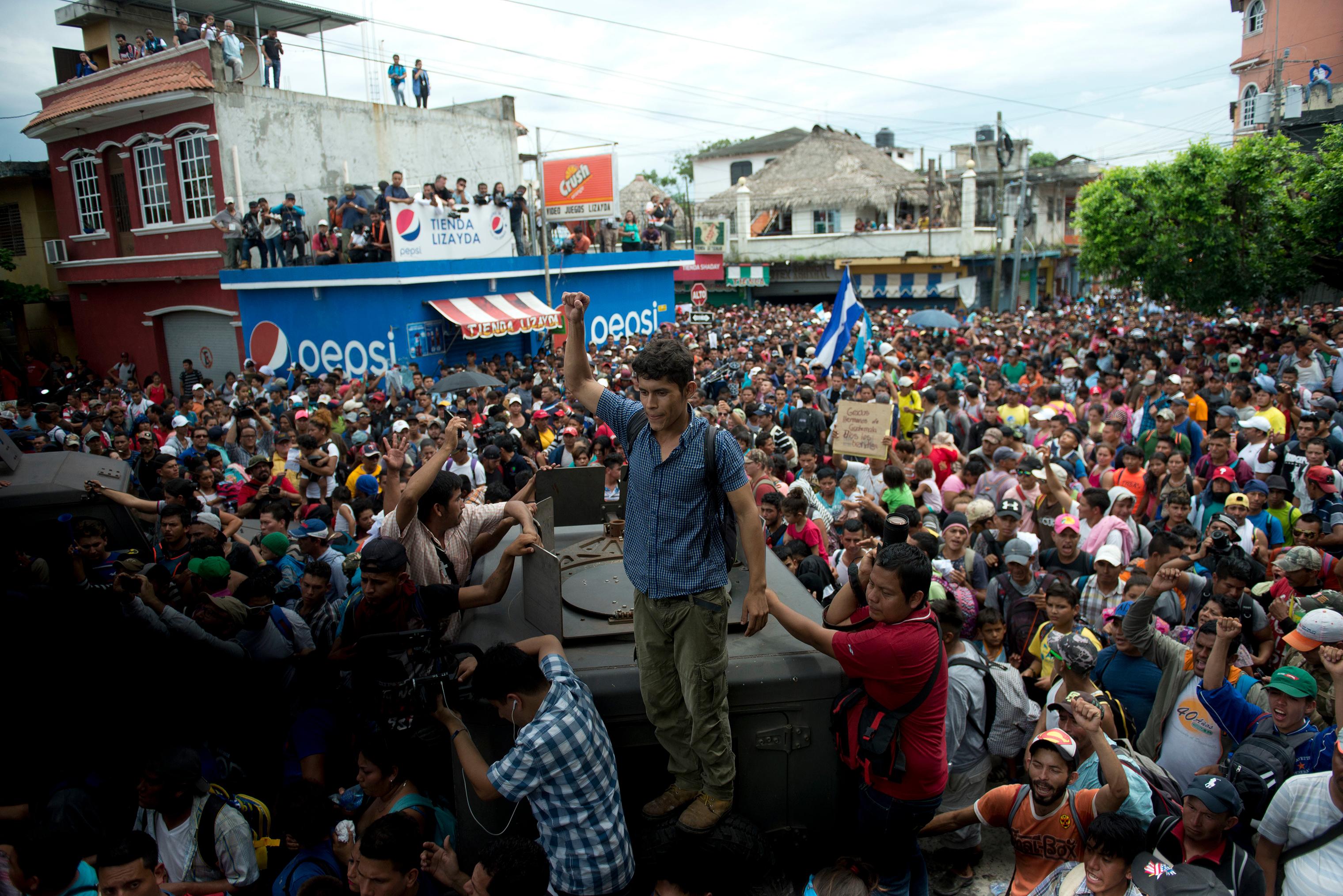 Thousands of Honduran migrants stream towards the border bridge in Tecun Uman, Guatemala, on Oct. 19.