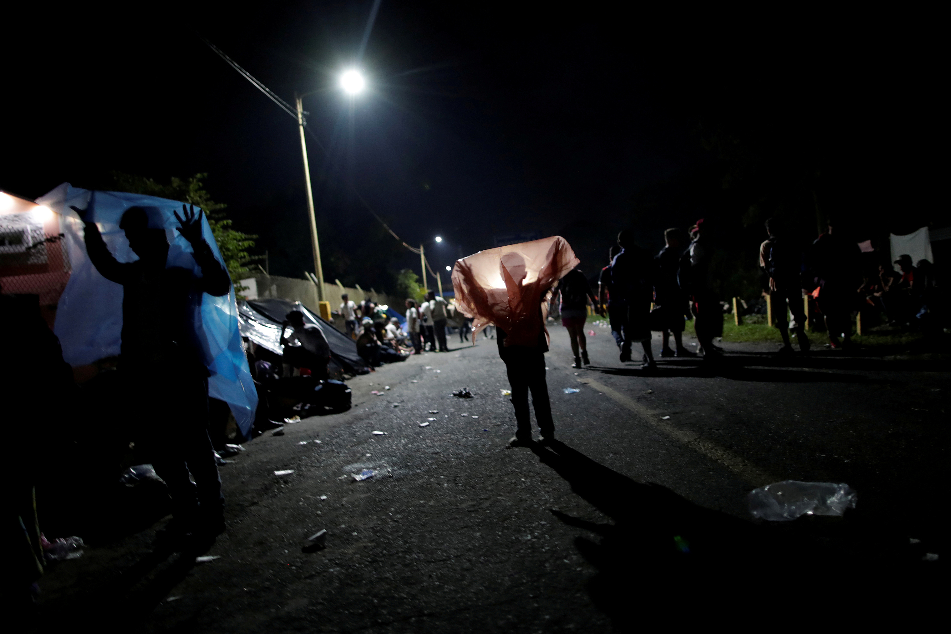 Honduran migrants play with plastic bags on the bridge that connects Mexico and Guatemala in Ciudad Hidalgo, Mexico, on Oct. 19.
