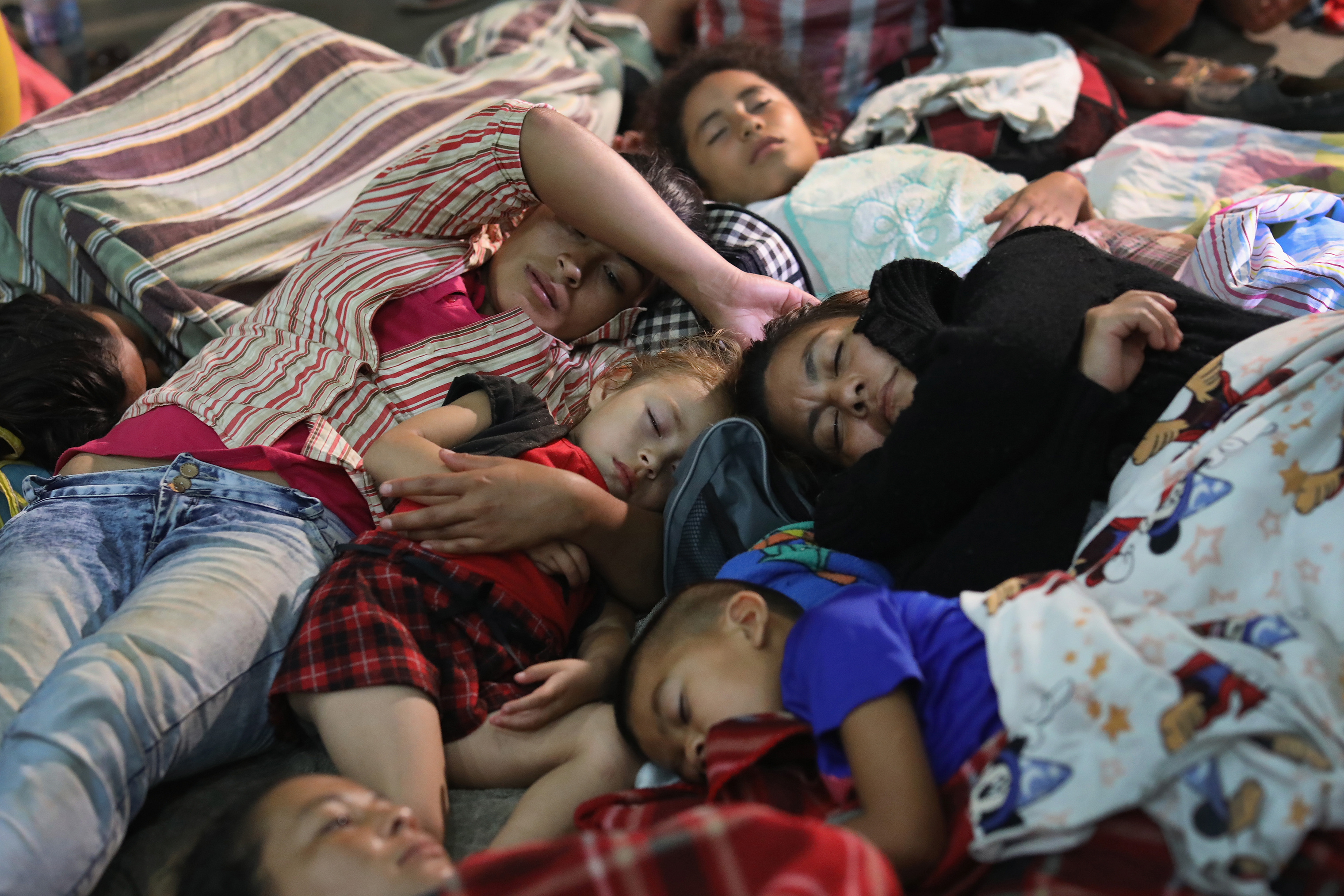 Families of immigrants rest for the night in a community gym in Chiquimula, Guatemala, on Oct. 16.