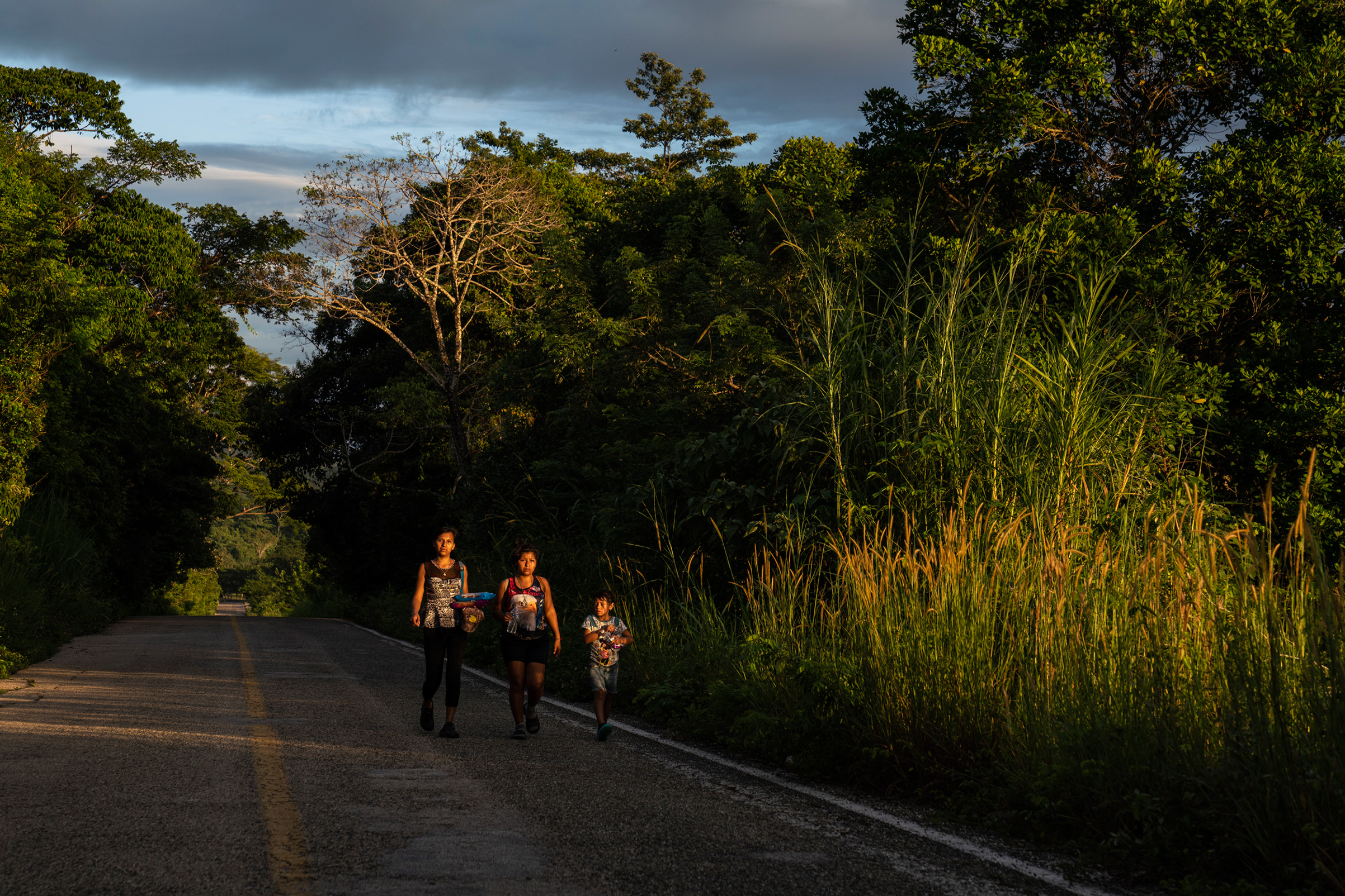 """Migrants walk through highway México 307 on Oct. 21, 2018, near Palenque, Chiapas. The highway is also known by locals as """"El gran corredor del pacífico del migrante,"""" or """"The Great Pacific Corridor of the Migrant. This is a common route for Honduran migrants due to the proximity to their country."""