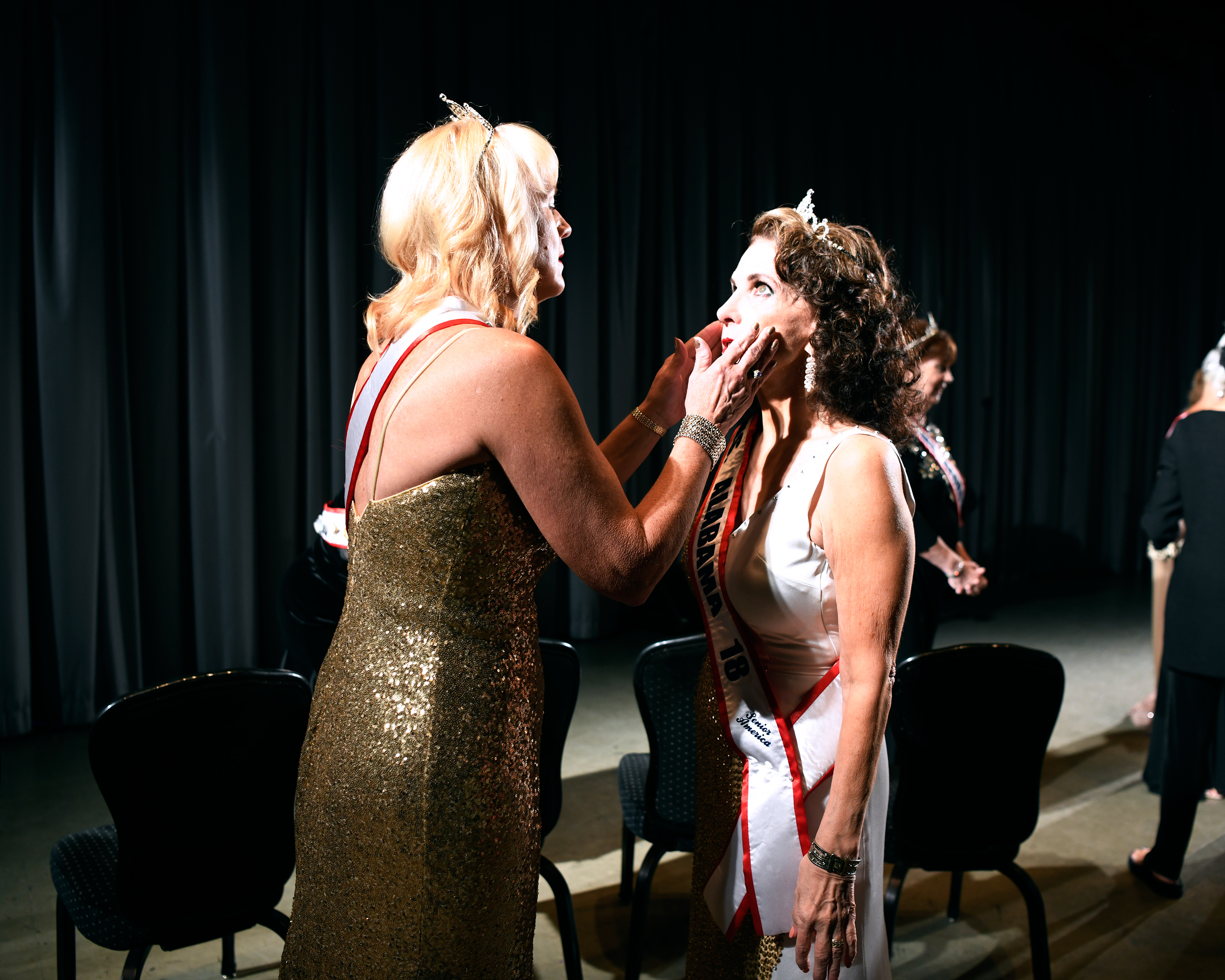 Kimberly Albrecht, Ms. Illinois, left, and Georgia Lee, Ms. Alabama, touch-up each other's makeup before a group photo.