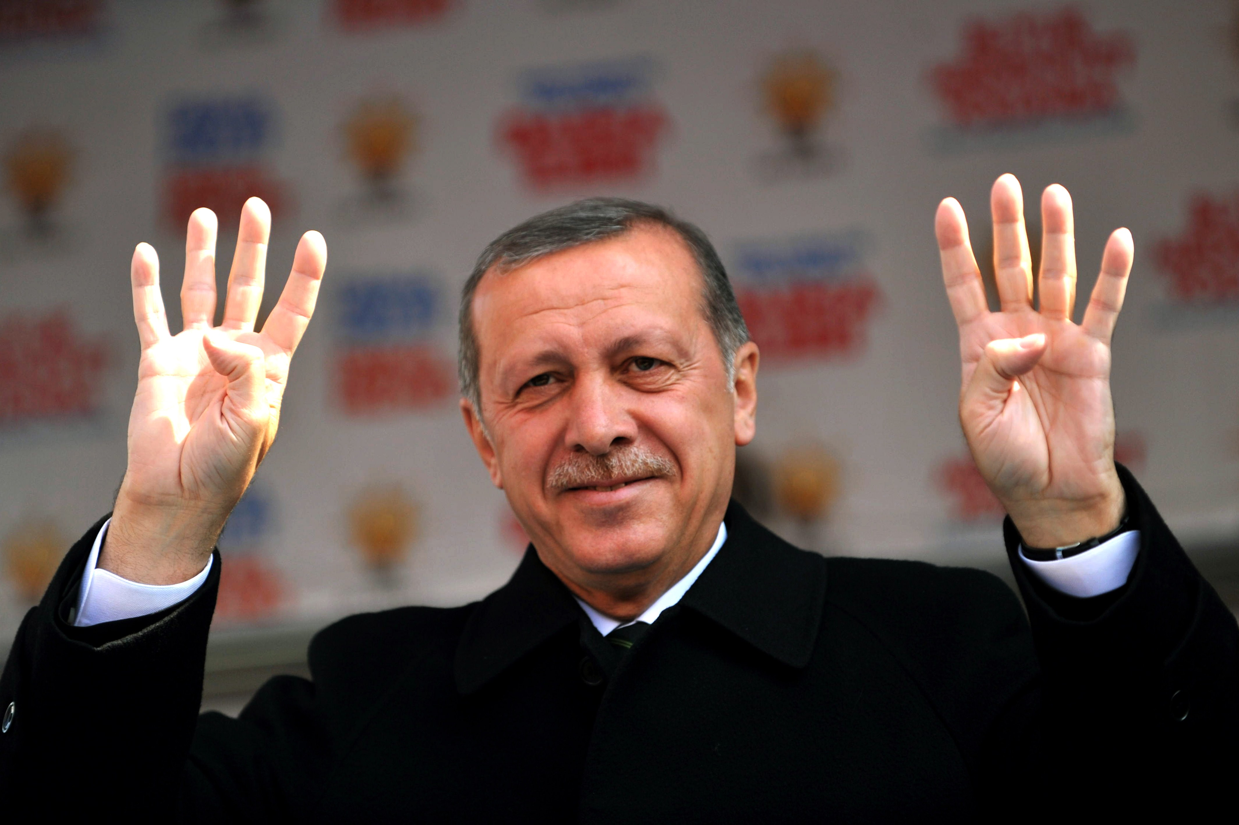 Turkish Prime Minister Recep Tayyip Erdogan waves the four finger sign of rabia during a rally of the Justice and Development Party in the Kartal district at the asia side of Istanbul on March 29, 2014.