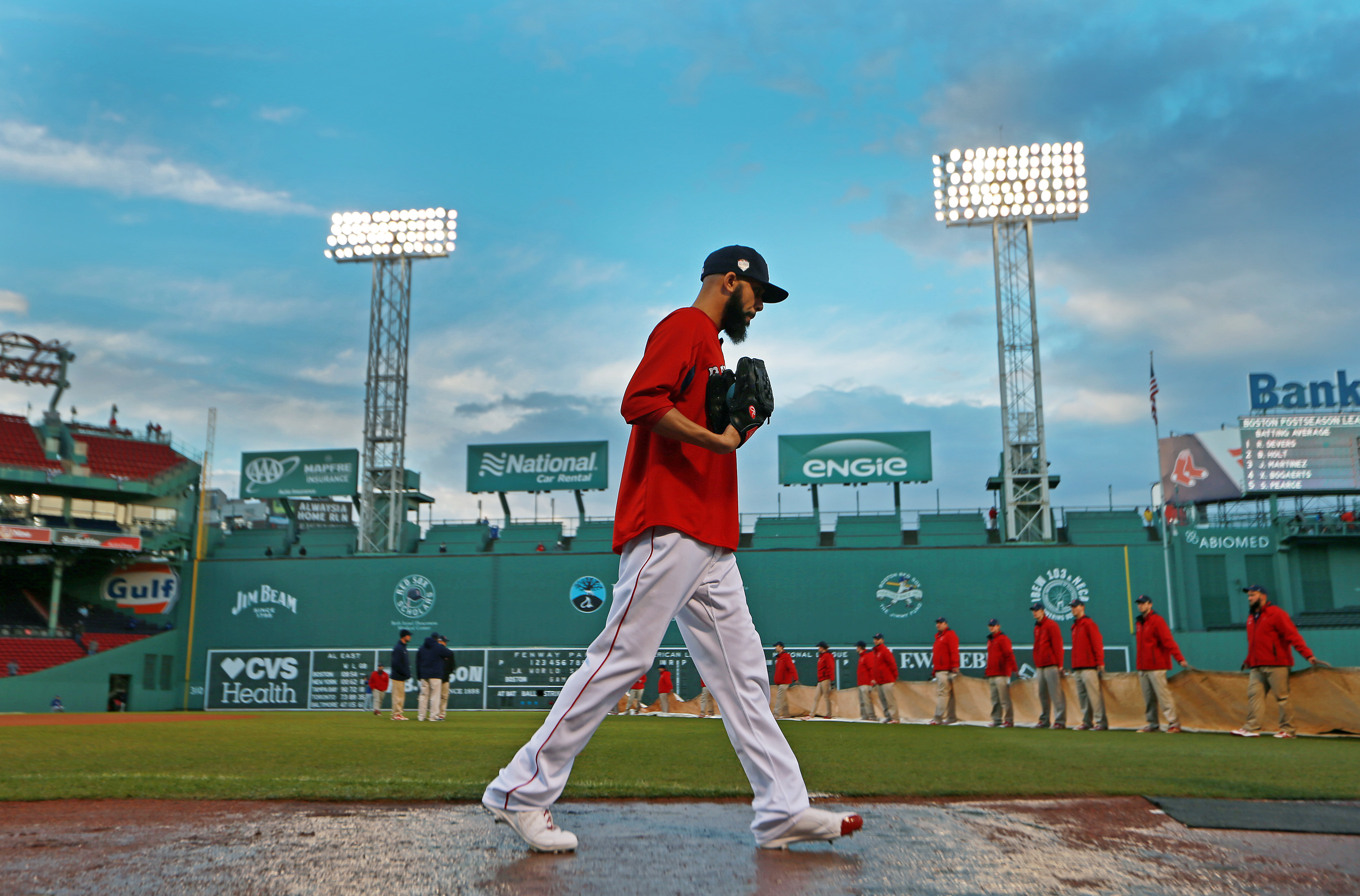 After a rain storm moved through the area, Red Sox Game Two scheduled starting pitcher David Price walked on the wet dirt, while in the background, the grounds crew, who had removed the tarp to clear it of standing water, were ready to put it back on over the infield. The Boston Red Sox hosted the Los Angeles Dodgers in Game One of the World Series at Fenway Park in Boston on Oct. 23, 2018.