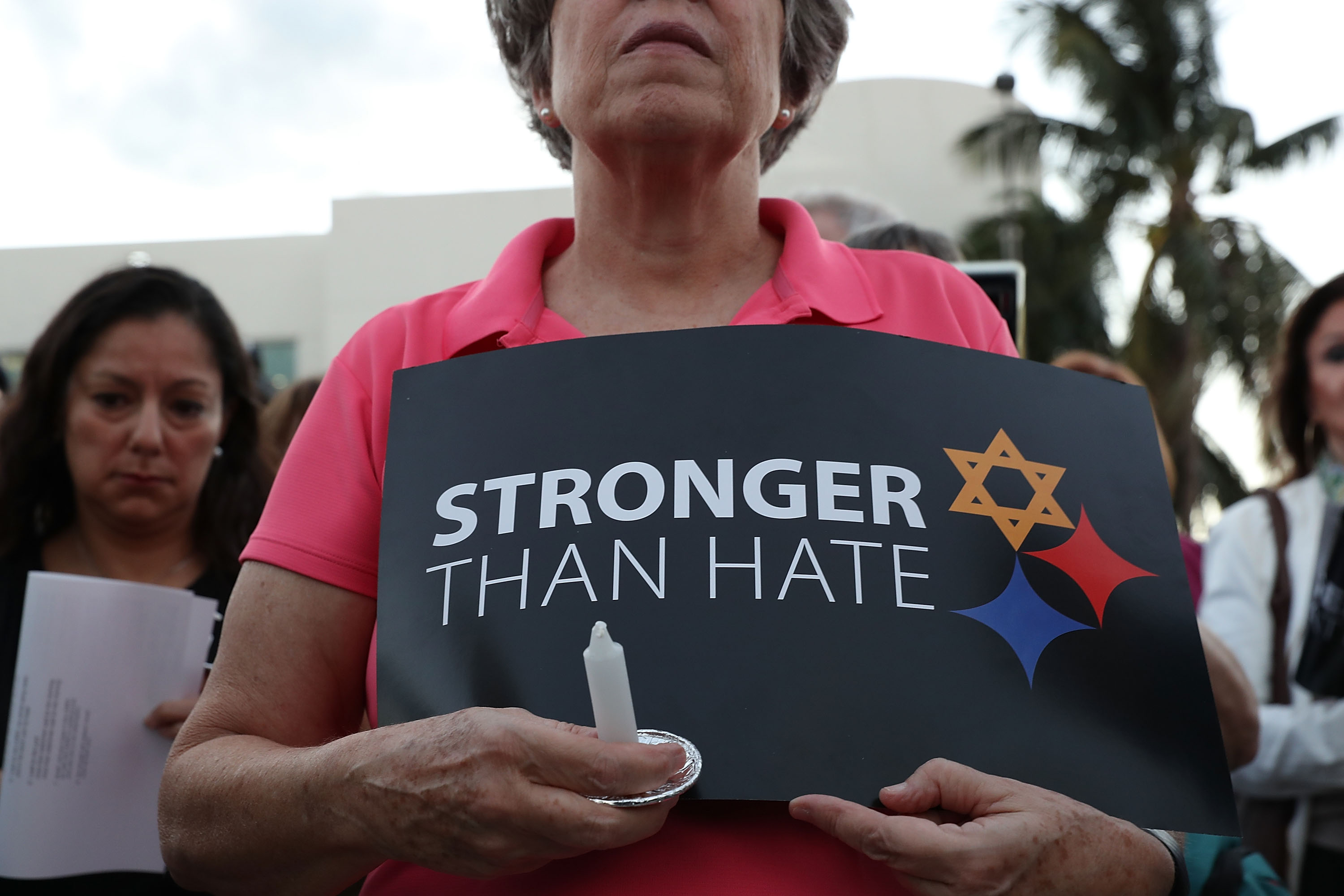 A person holds a sign that reads, 'Stronger than Hate,' as she joins with others for a Community-Wide Solidarity Vigil at the Holocaust Memorial Miami Beach to remember the victims of the mass shooting at a Pittsburgh temple on October 30, 2018 in Miami Beach, Florida.