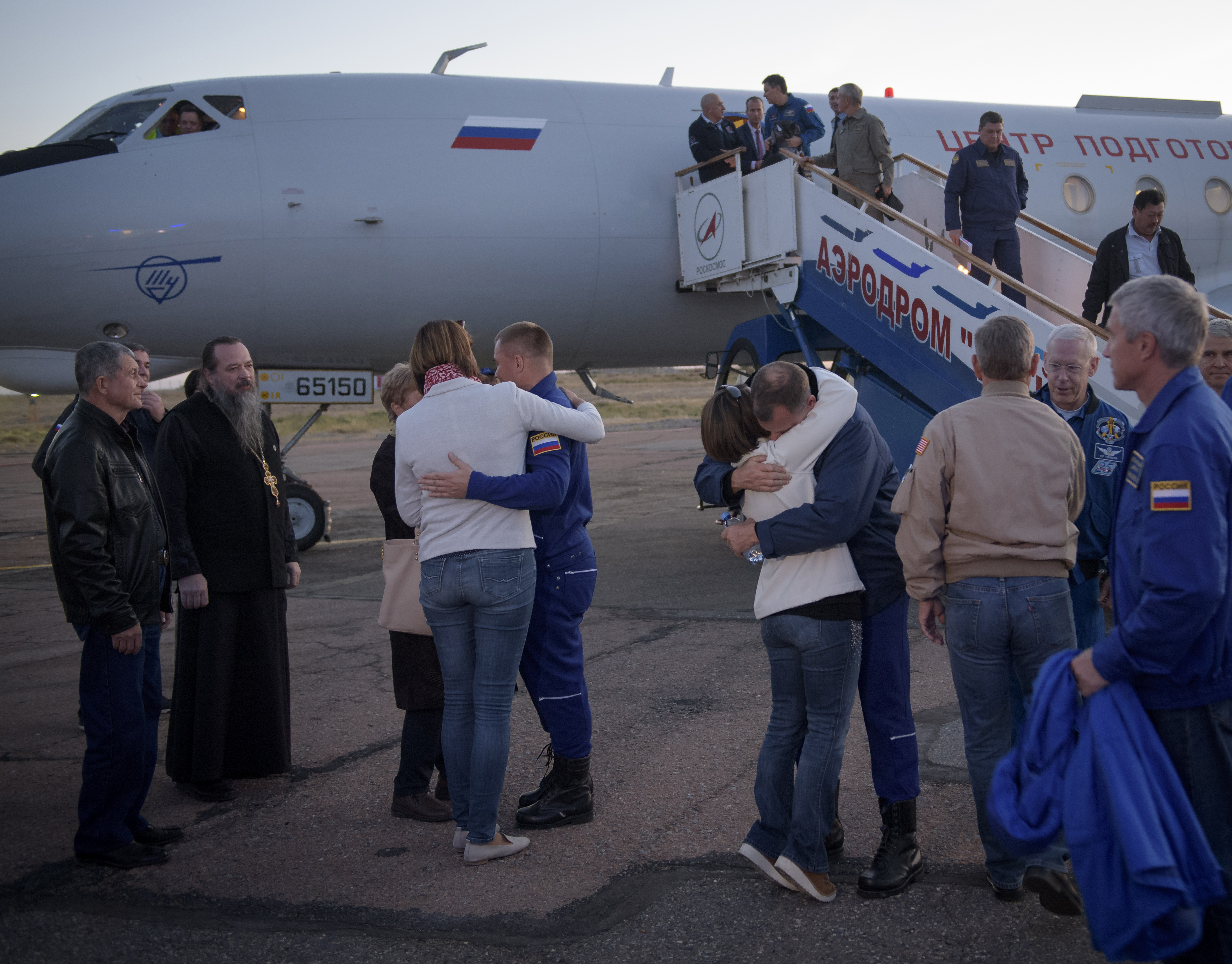 Expedition 57 Flight Engineer Alexey Ovchinin of Roscosmos, left, and Flight Engineer Nick Hague of NASA, right. embrace their families after landing at the Krayniy Airport, Thursday, Oct. 11, 2018 in Baikonur, Kazakhstan.
