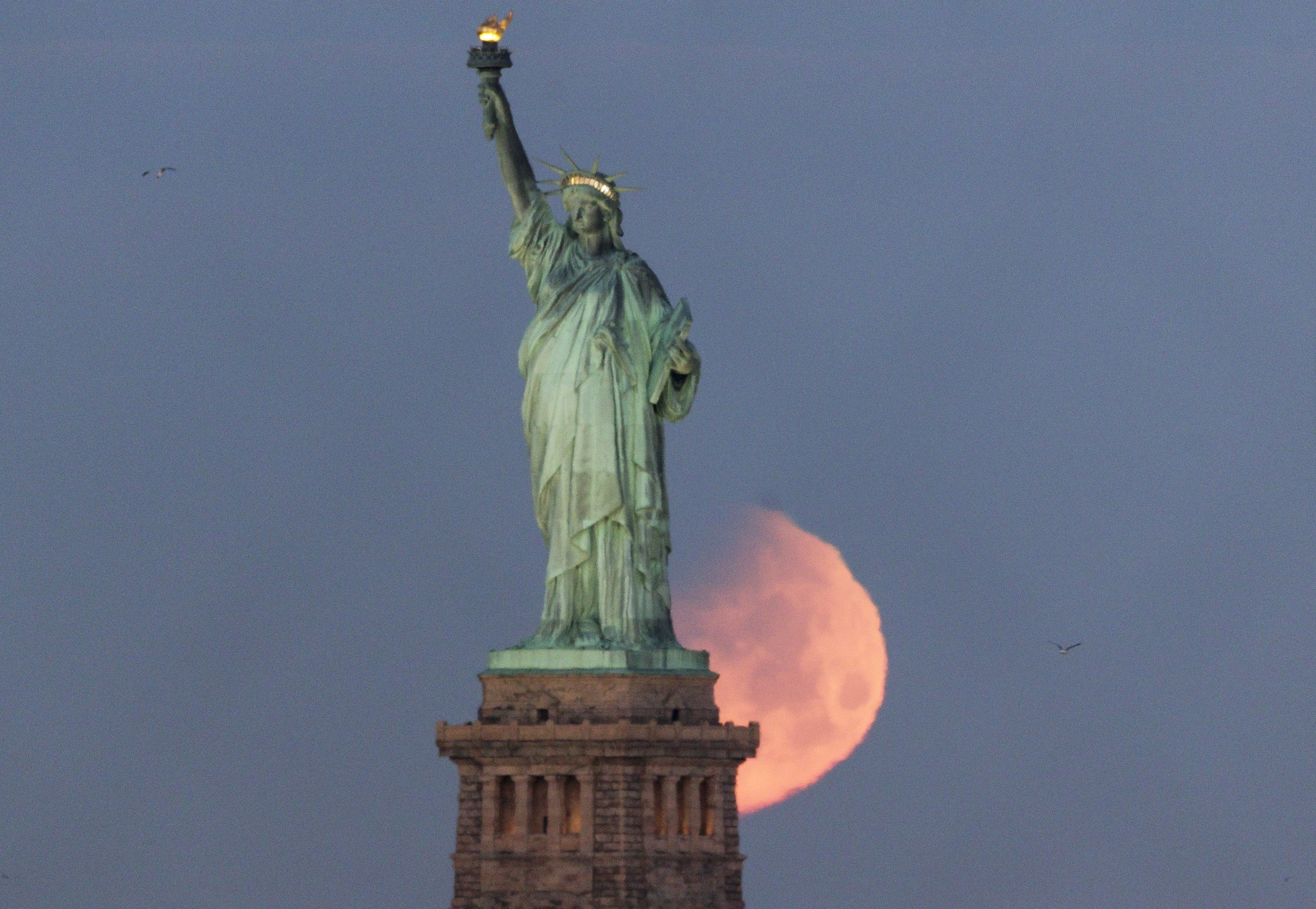 The moon sets behind the Statue of Liberty in New York on Jan. 31, 2018.