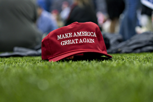 A 'Make America Great Again' hat sits on the ground ahead of a speech by U.S. President Donald Trump during a rally in Washington, Michigan, U.S., on Saturday, April 28, 2018.