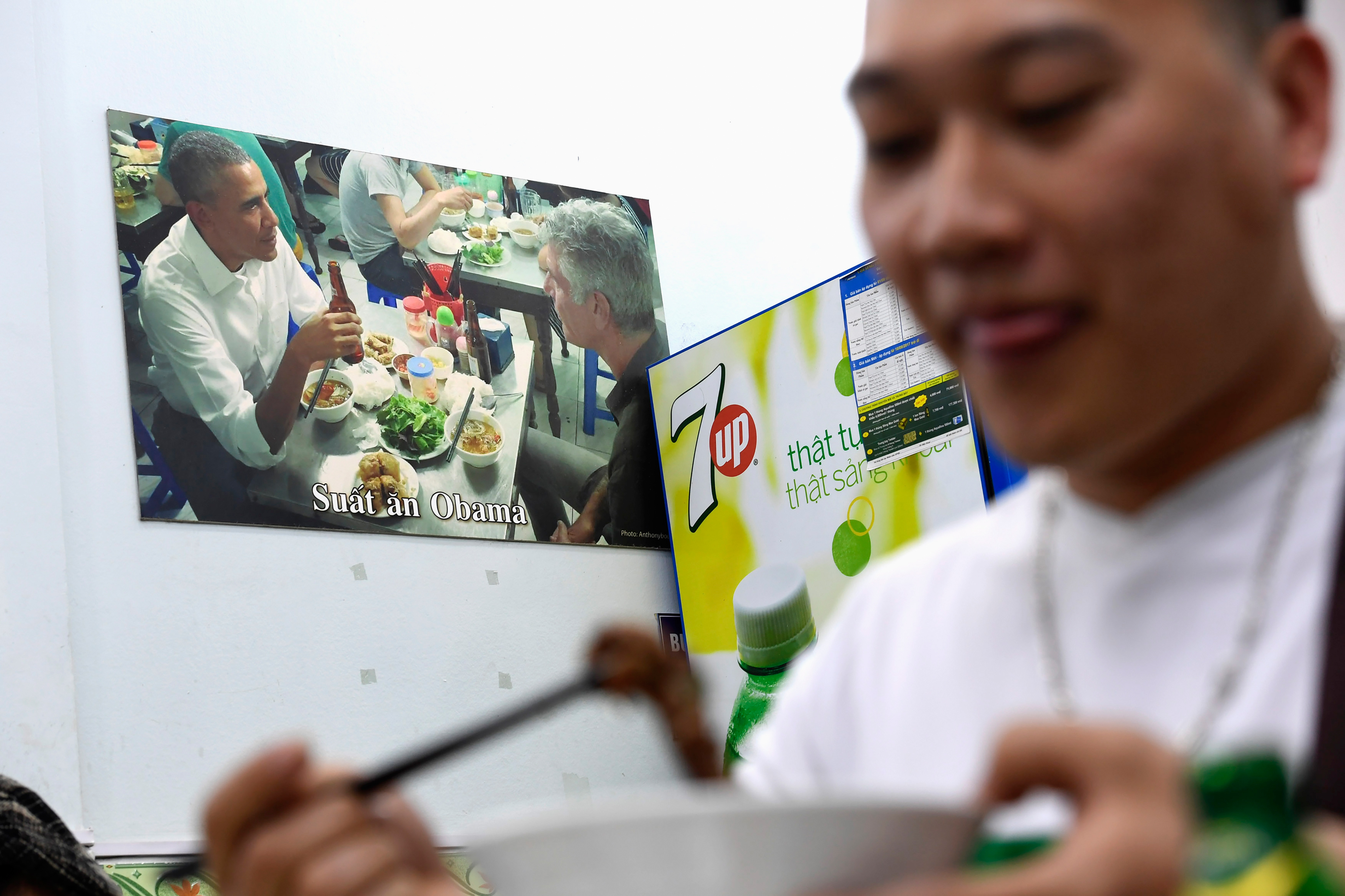 In this photograph taken on March 20, 2018, a customer enjoys a meal at Bun Cha Huong Lien restaurant, now dubbed  bun cha Obama  with a photograph of former U.S. President Barack Obama displayed on the wall, in Hanoi's old quarter.