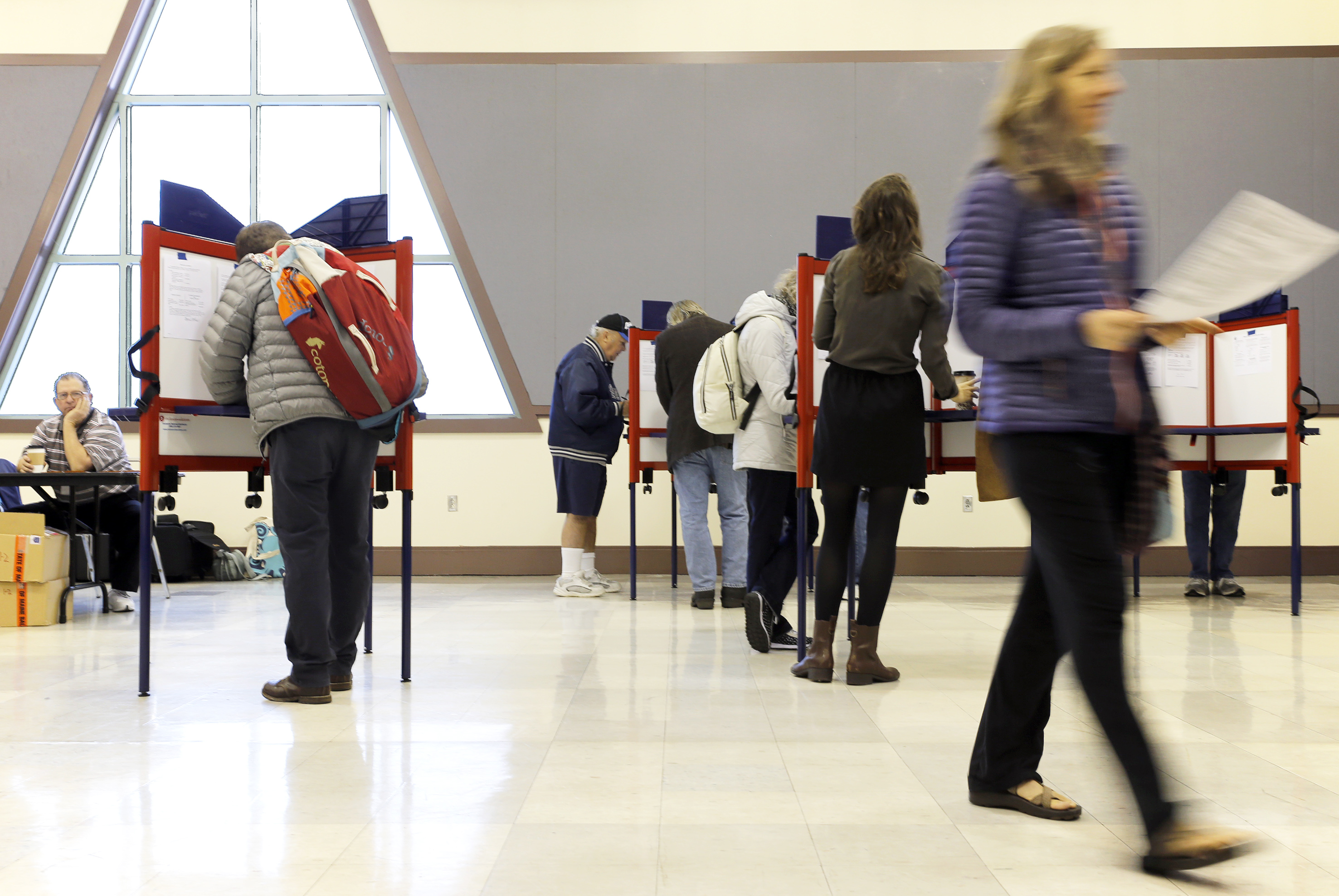 Sue Vittner, right, walks her completed ballot to the scanning booth at the Merrill Auditorium voting station Tuesday morning. Turnout at the station has been pretty good, according to Election Warden Carol . Democrats are paying emphasis to the Secretary of State since they are administering the ballots for the 2018 Midterm Elections. (Staff photo by Ben McCanna/Portland Press Herald via Getty Images)