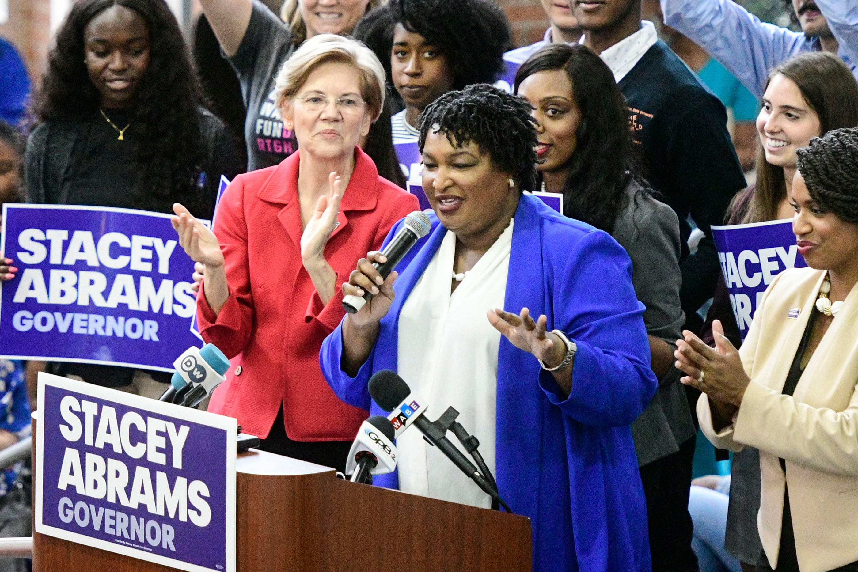 Democratic Georgia gubernatorial nominee Stacey Abrams (C) speaks to supporters while flanked by Boston City Council woman Ayanna Pressley (R) and Democratic Senator from Massachusetts Elizabeth Warren during a campaign rally in Morrow, Georgia, USA, October 9, 2018.