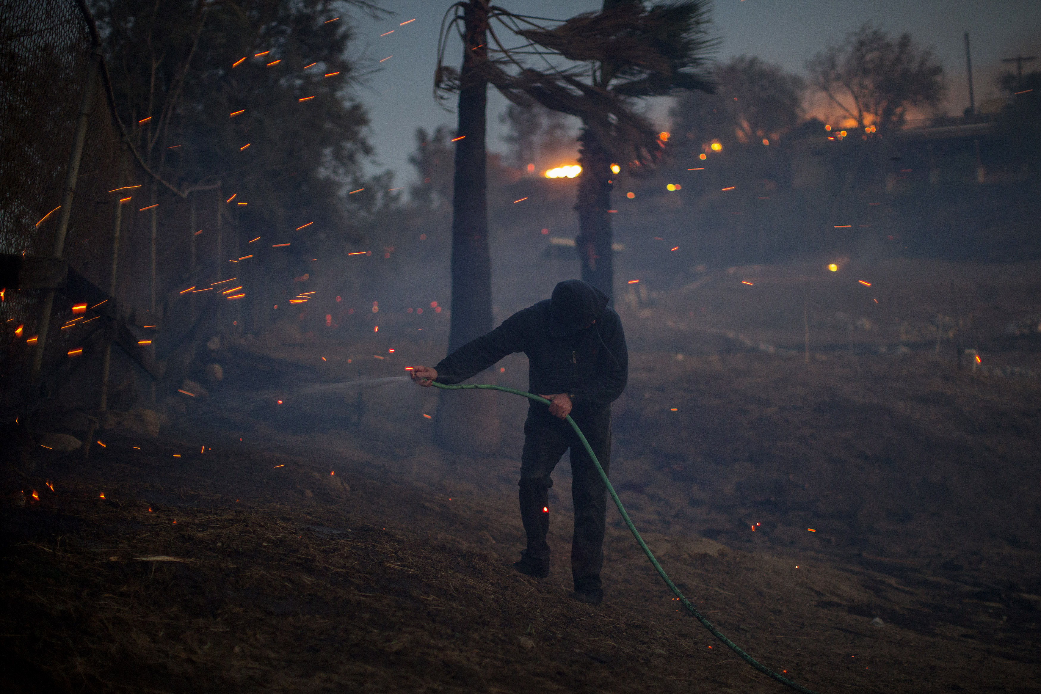 A strong wind blows embers around a resident hosing his burning property during the Creek Fire on December 5, 2017 in Sunland, California.