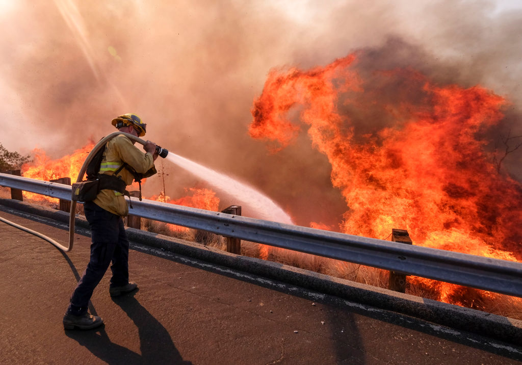 A firefighter battles wildfire near a freeway in Simi Valley, California, the United States on Nov. 13, 2018.