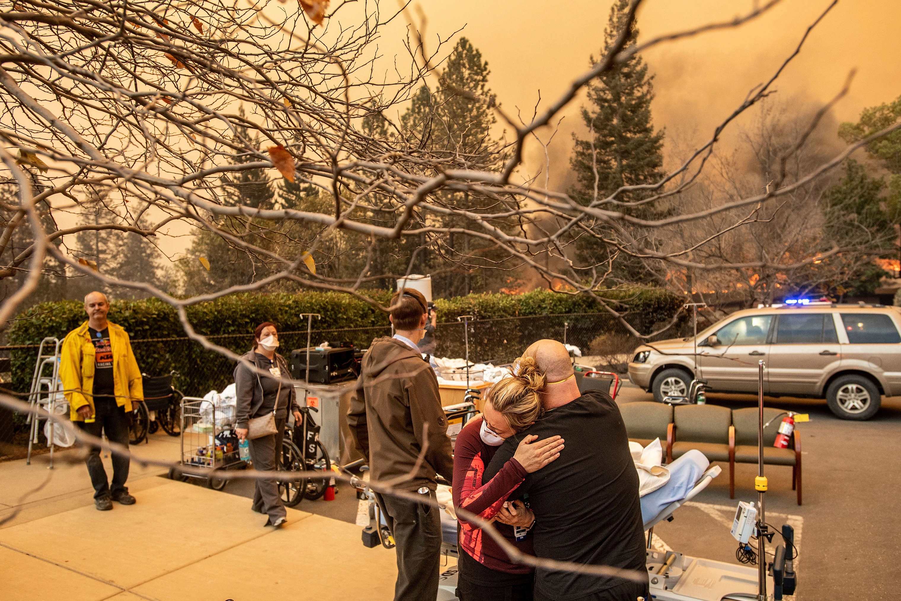 Nurse Cassie Lerossignol hugs a coworker as the Feather River Hospital burns while the Camp Fire rages through Paradise, Calif., on Nov. 8.