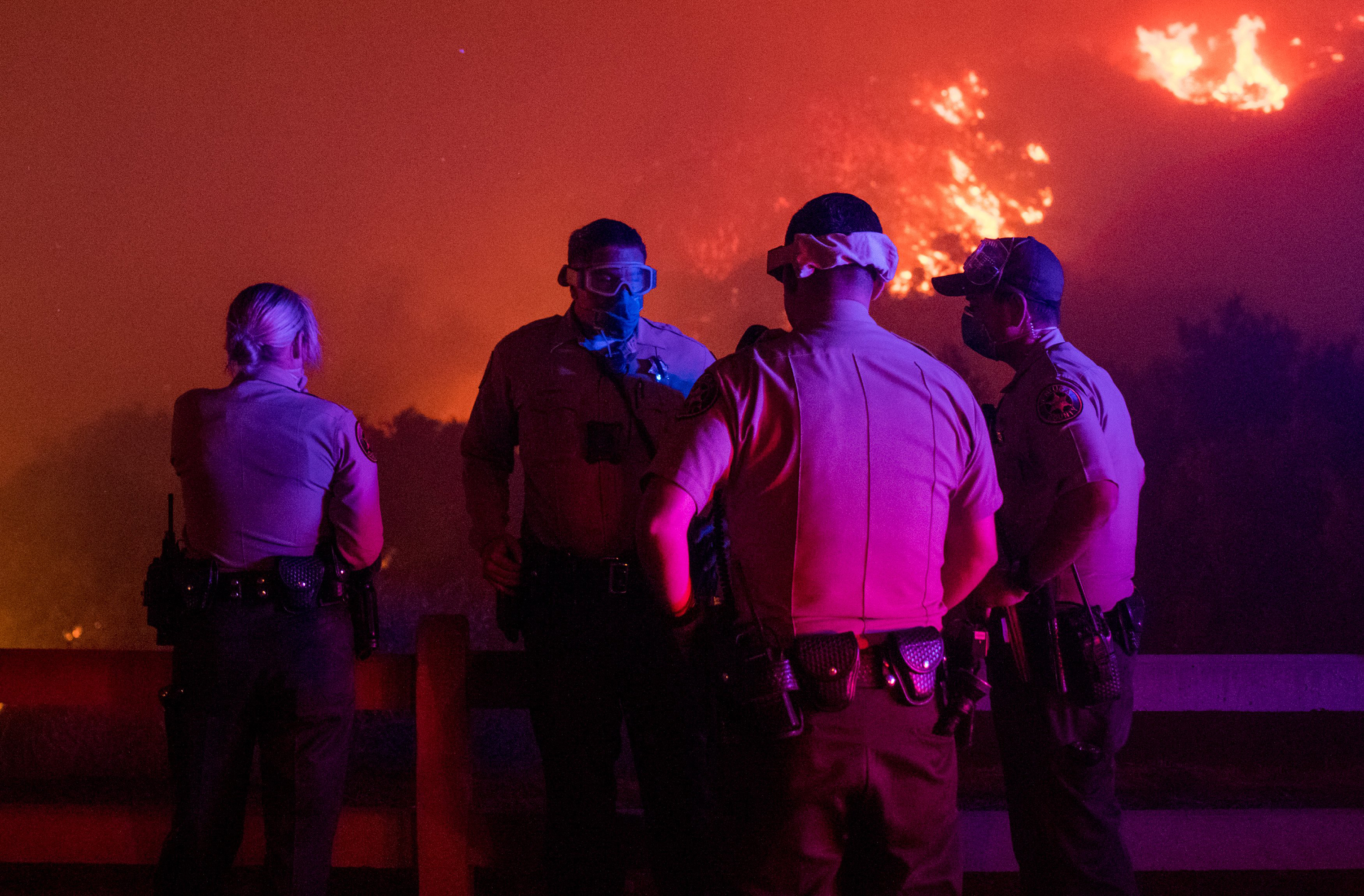 Local law enforcement standby to give mandatory evacuation orders to residents in Thousand Oaks, Calif. as the Wooolsey fire burns over 8,000 acres on Nov. 8.