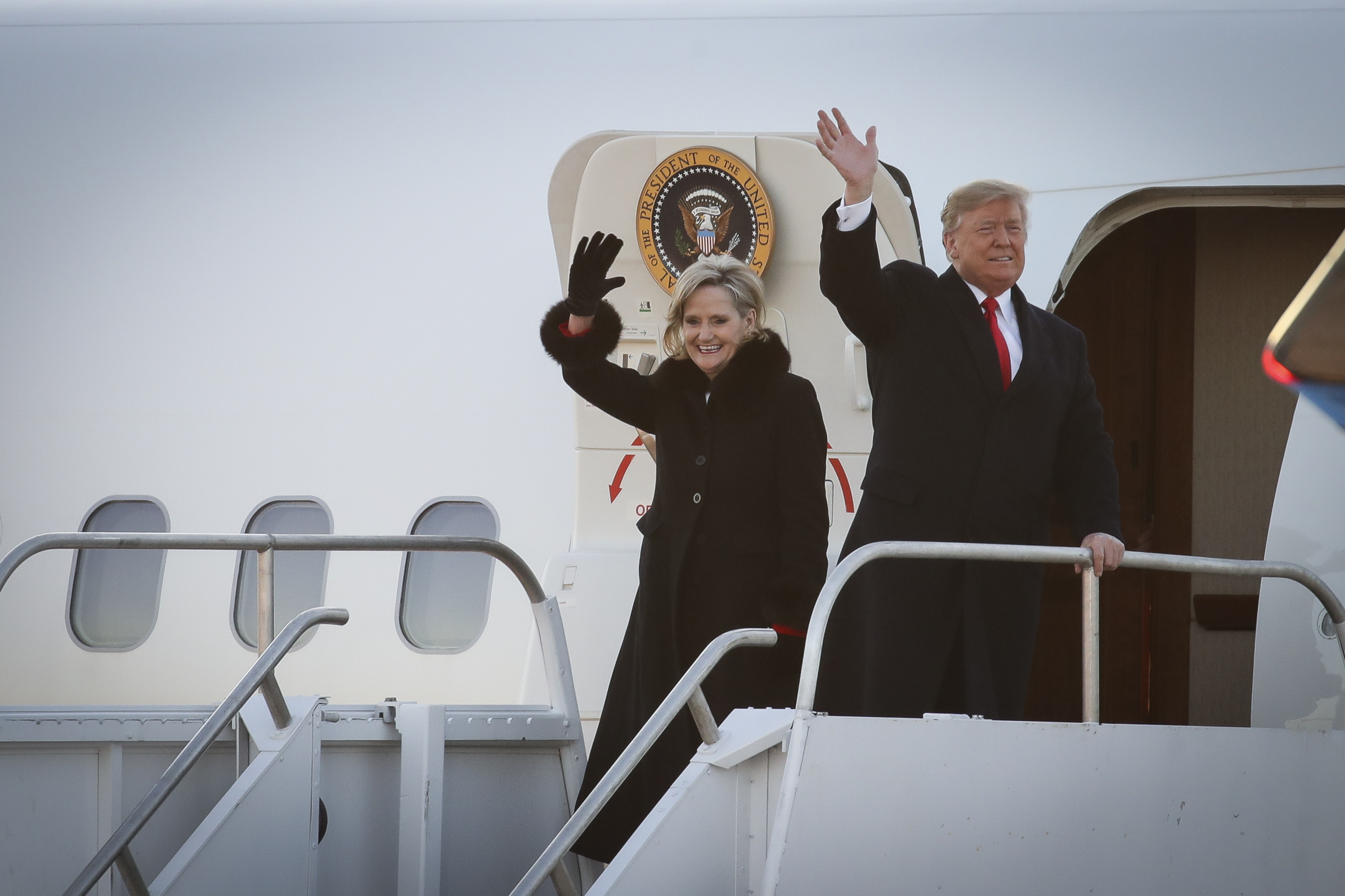 Republican candidate for U.S. Senate Cindy Hyde-Smith and President Donald Trump wave as they exit Air Force One as they arrive for a rally at the Tupelo Regional Airport, November 26, 2018 in Tupelo, Mississippi.