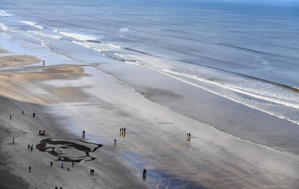 Members of the public gather around a portrait drawn in the sand of British Army Staff Nurse Rachael Ferguson (1886-26 June 1918) on Downhill beach, for filmmaker Danny Boyle Pages of the Sea, commissioned by 14-18 NOW to mark the centenary of Armistice Day on November 11, 2018