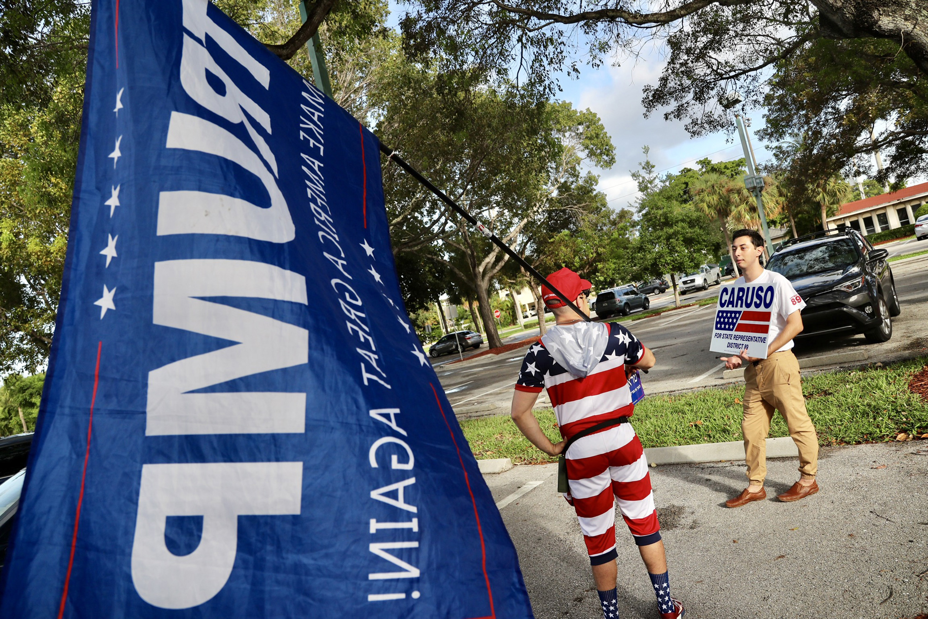 Mike Caruso campaign employee Isaac Rheinbolt, chats with a Trump supporter, who did not want to be identified, in the parking lot of the Boca Raton Community Center on Election Day.