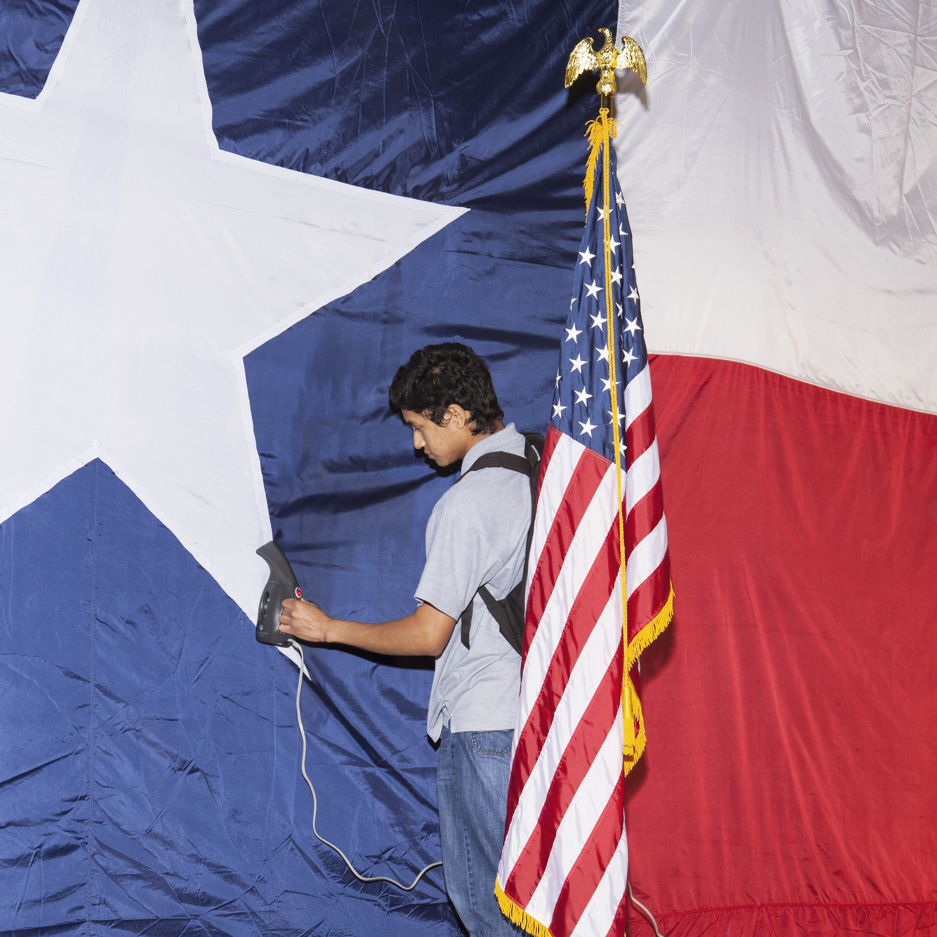 Jose Maybit Lopez, an intern for Texas Sen. Ted Cruz, steams a flag in preparation for the Election Night party in Houston.