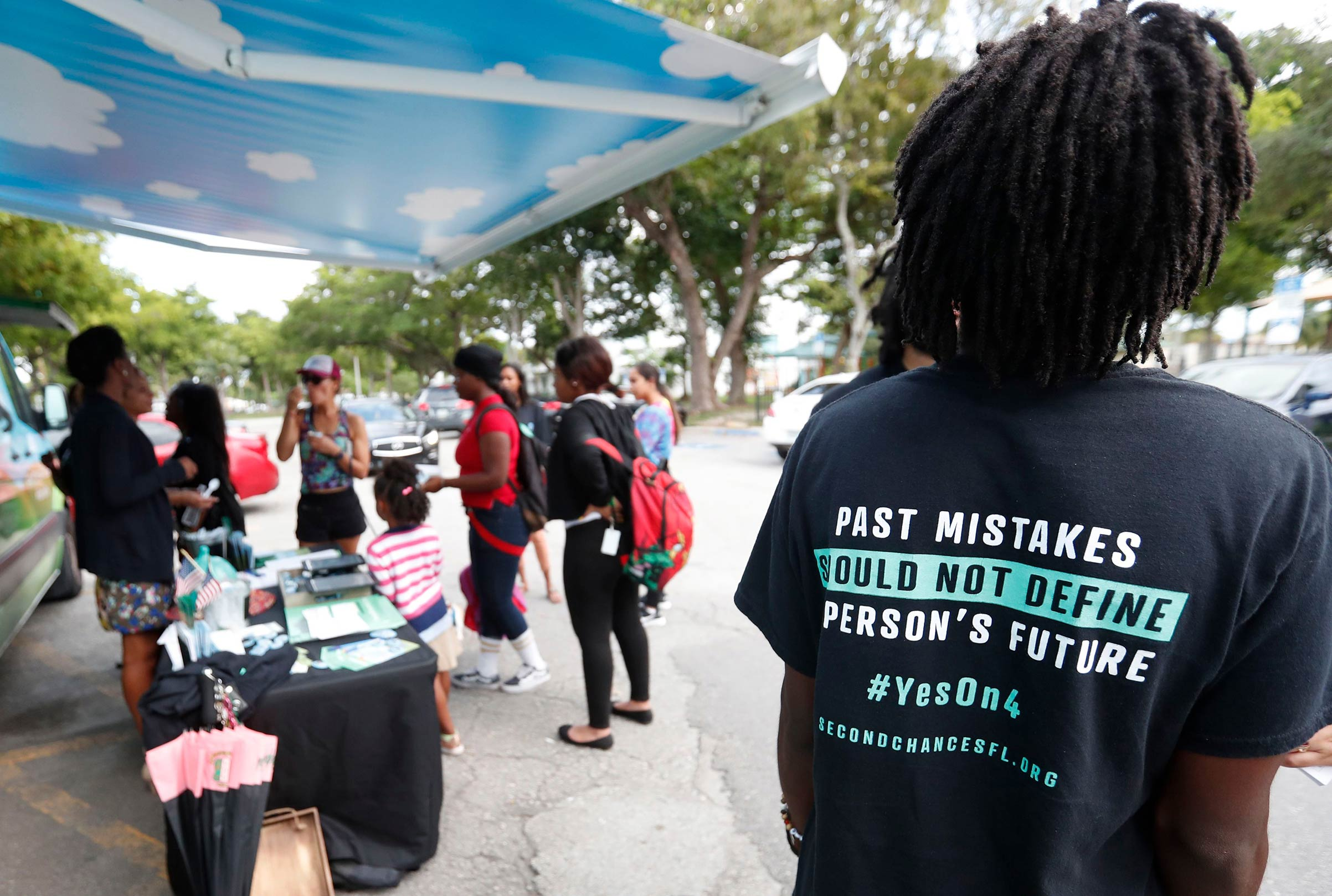 People gather around the Ben & Jerry's  Yes on 4  truck as they learn about Amendment 4 and eat free ice cream at Charles Hadley Park in Miami on Oct. 22, 2018.