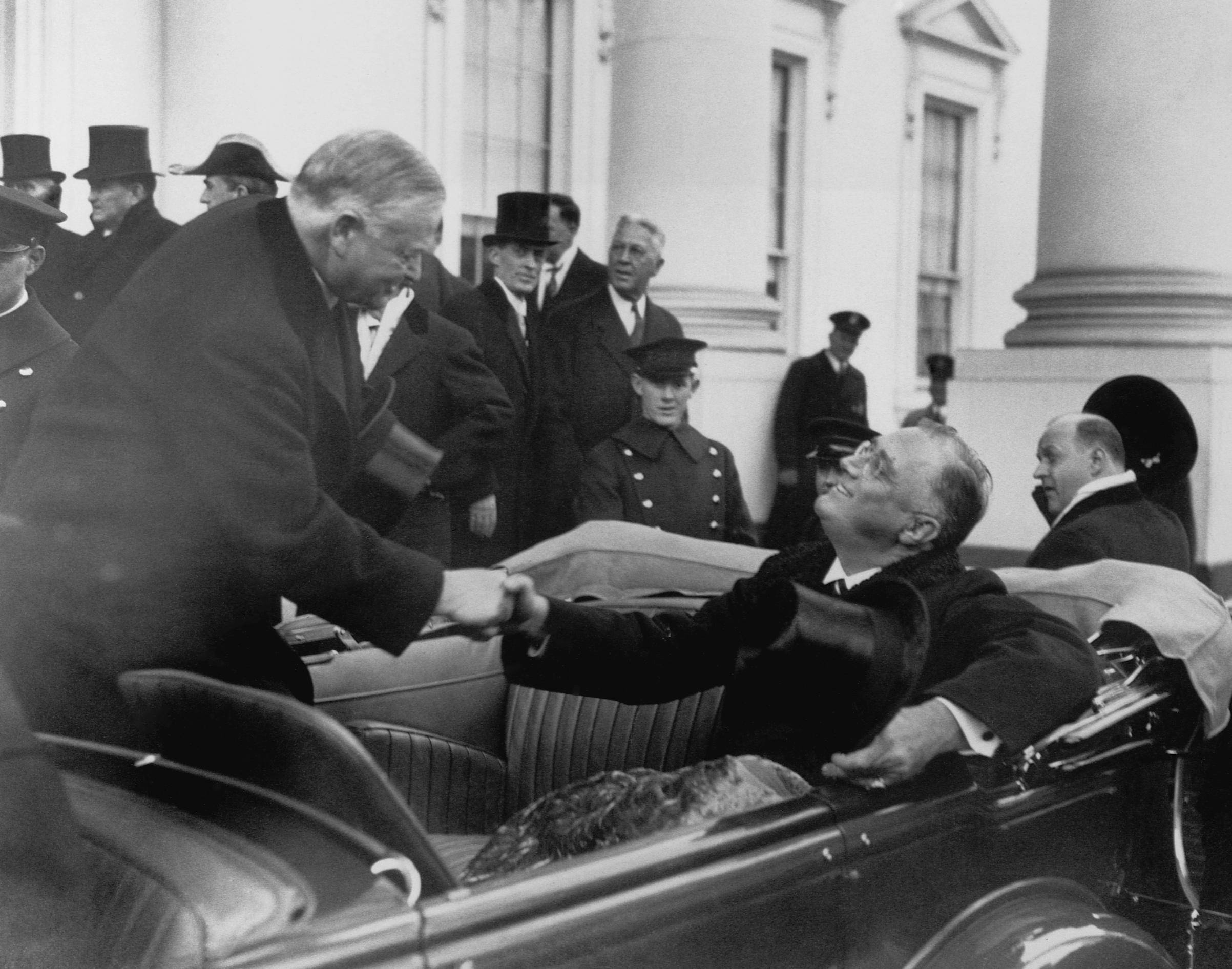 Outgoing President Herbert Hoover shakes the hand of incoming Franklin Roosevelt after Roosevelt's inauguration