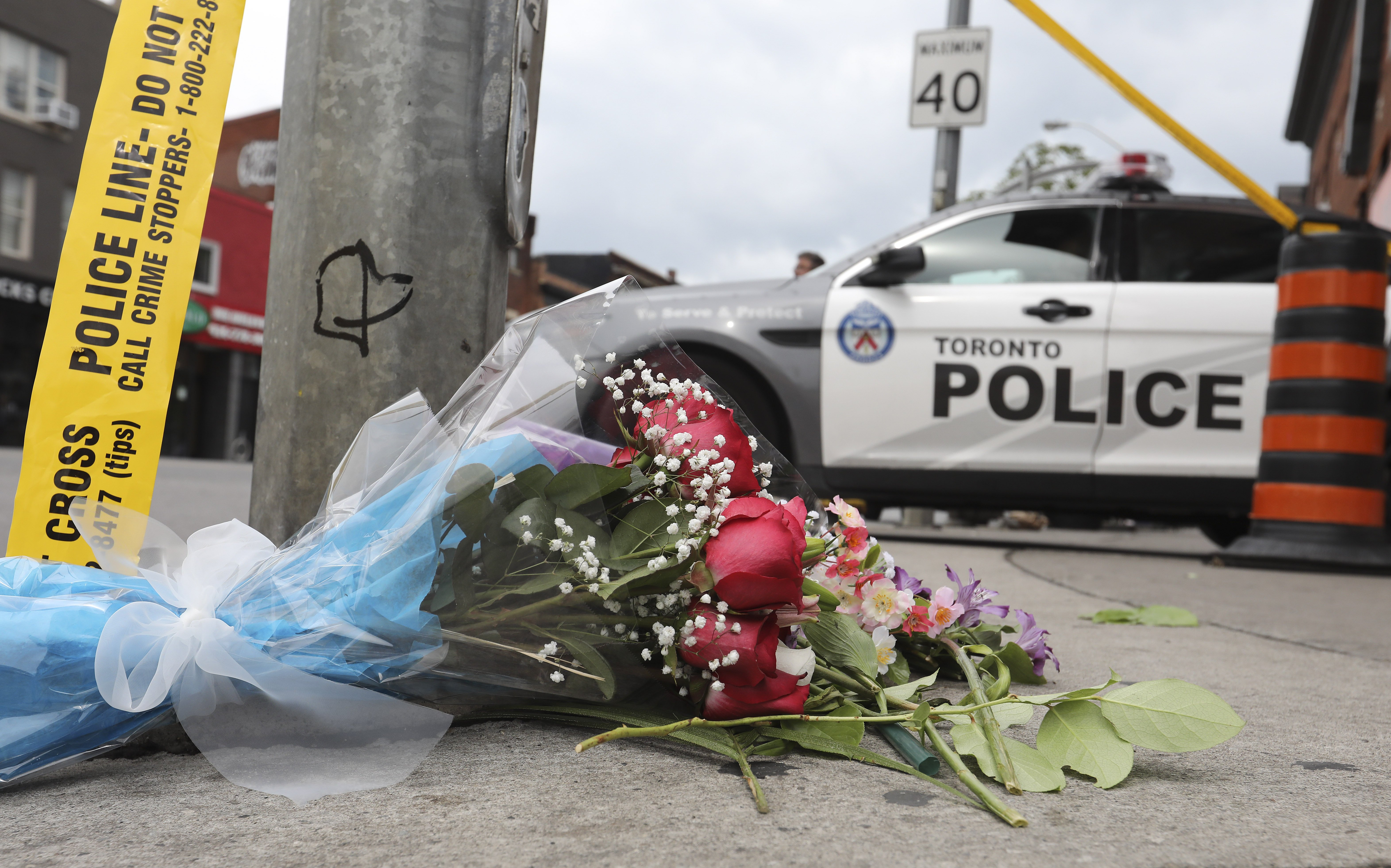 A makeshift memorial commemorates a mass shooting that killed two on Danforth Avenue in Toronto, Ontario on July 22, 2018.