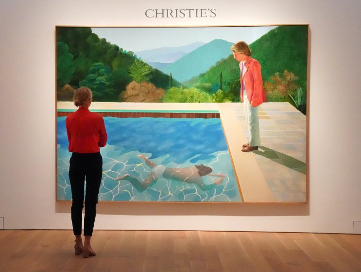 """A woman looks at David Hockneys """"Portrait of an Artist (Pool with Two Figures)"""" during a press preview on September 13, 2018 at Christie's New York. - The painting is to be auctioned during Christie's November 2018 Evening Sale of Post-War and Contemporary Art. Christie's expects the painting to sell for 80 million USD, making the work the most valuable piece of art by a living artist ever sold at auction."""