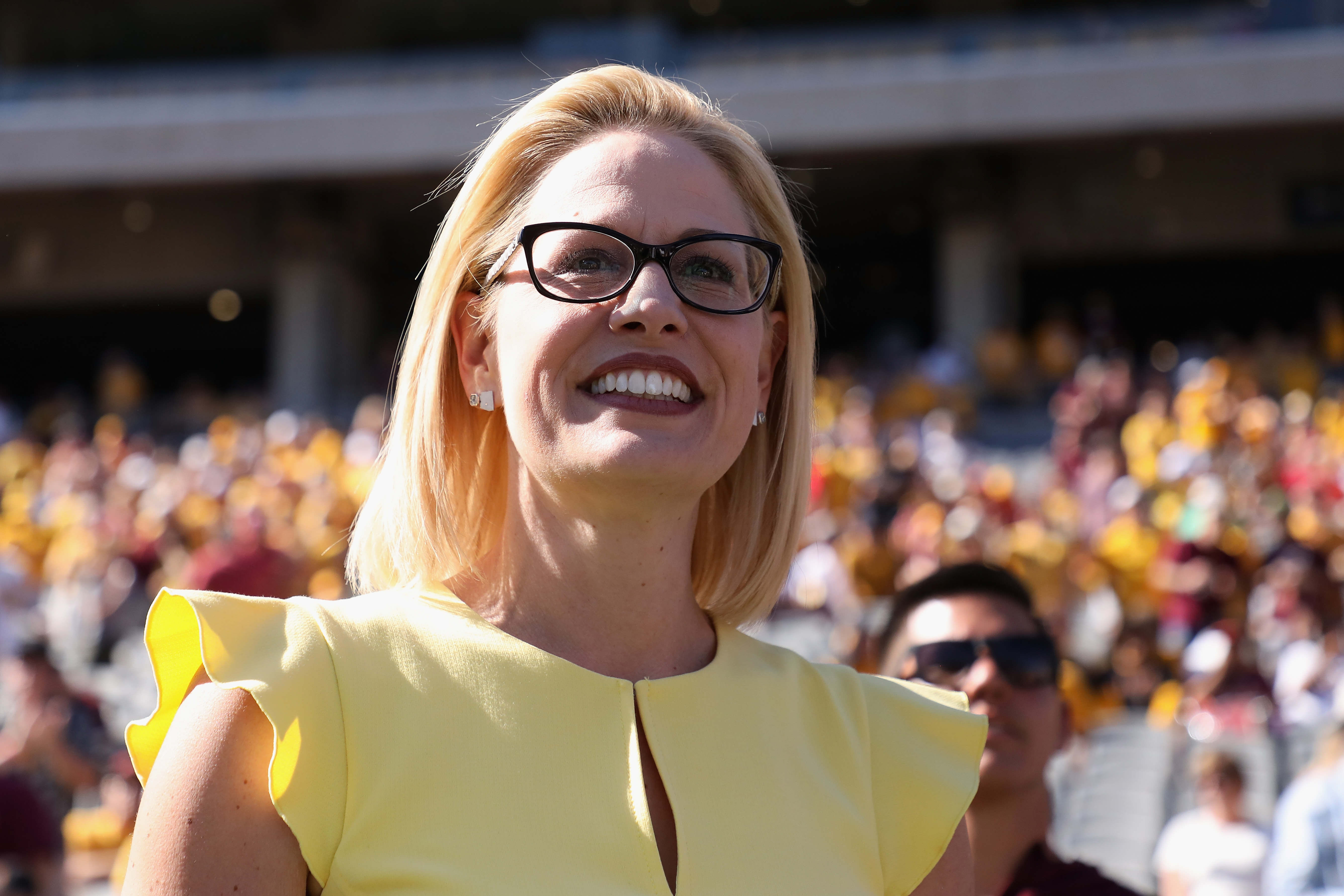 Democrat Senate candidate Kyrsten Sinema participates in the pregame coin toss before the game between the Utah Utes and the Arizona State Sun Devils on Nov. 3, 2018 in Tempe, Arizona.