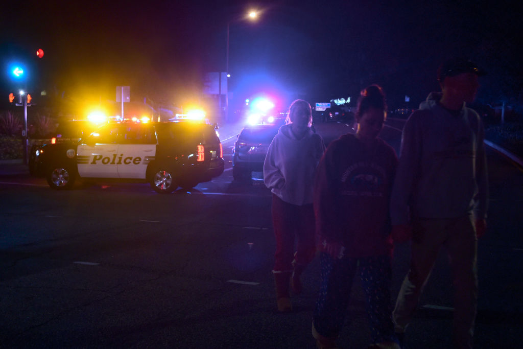 People walk away from the scene as it unfurls at the intersection of US 101 freeway and the Moorpark Rad exit as police vehicles close off the area responding to a shooting at a bar in Thousand Oaks, California on November 8, 2018.